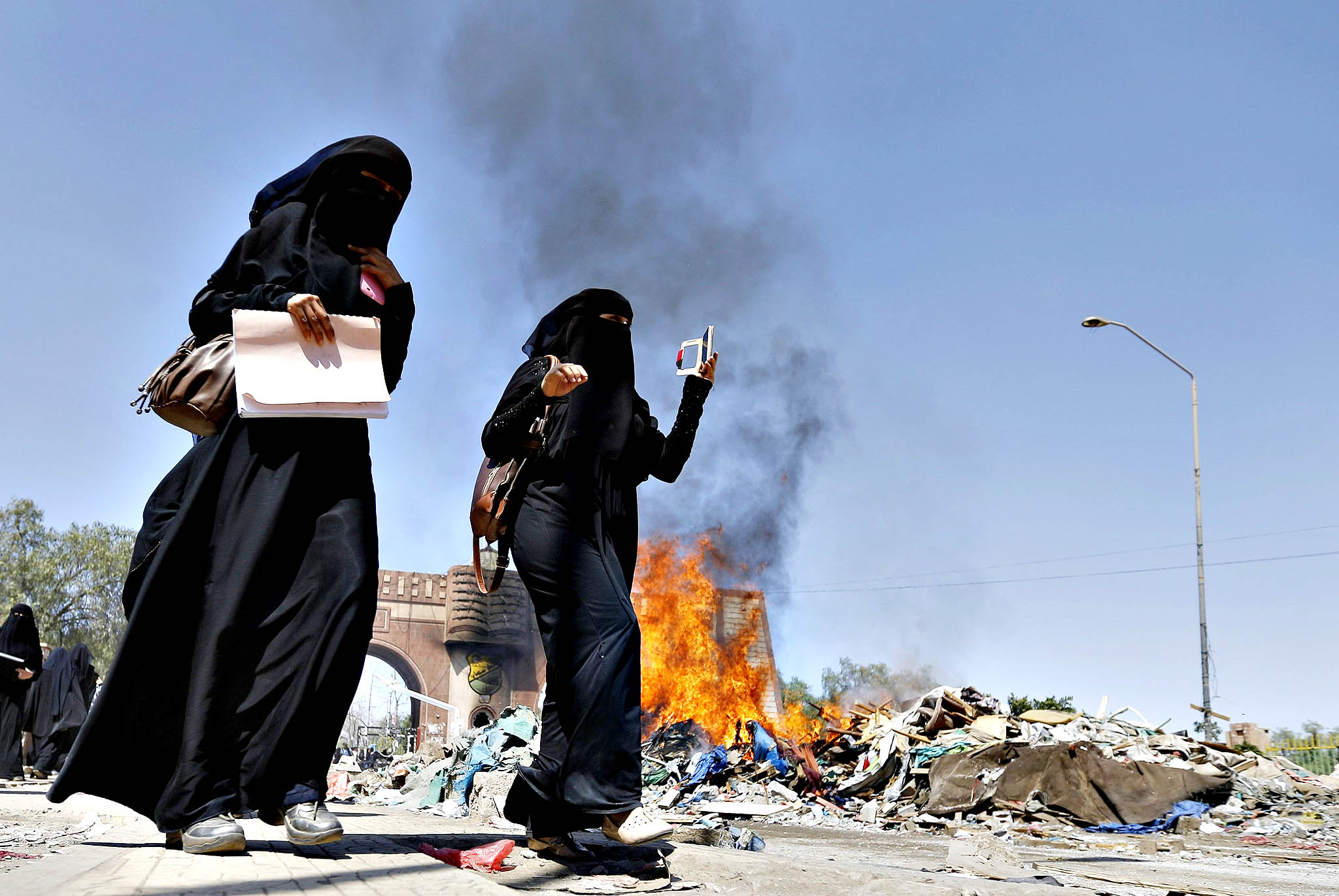 Women walk past demolished huts set on fire at Taghyeer (Change) Square in Sanaa November 10, 2014. Authorities had deployed riot police and used bulldozers to demolish the huts set up by pro-democracy protesters when they had camped in the square to demand a regime change in 2011. These temporary shelters had not been removed from the square after protesters vacated it last year. It was not immediately apparent who had set the demolished huts on fire.