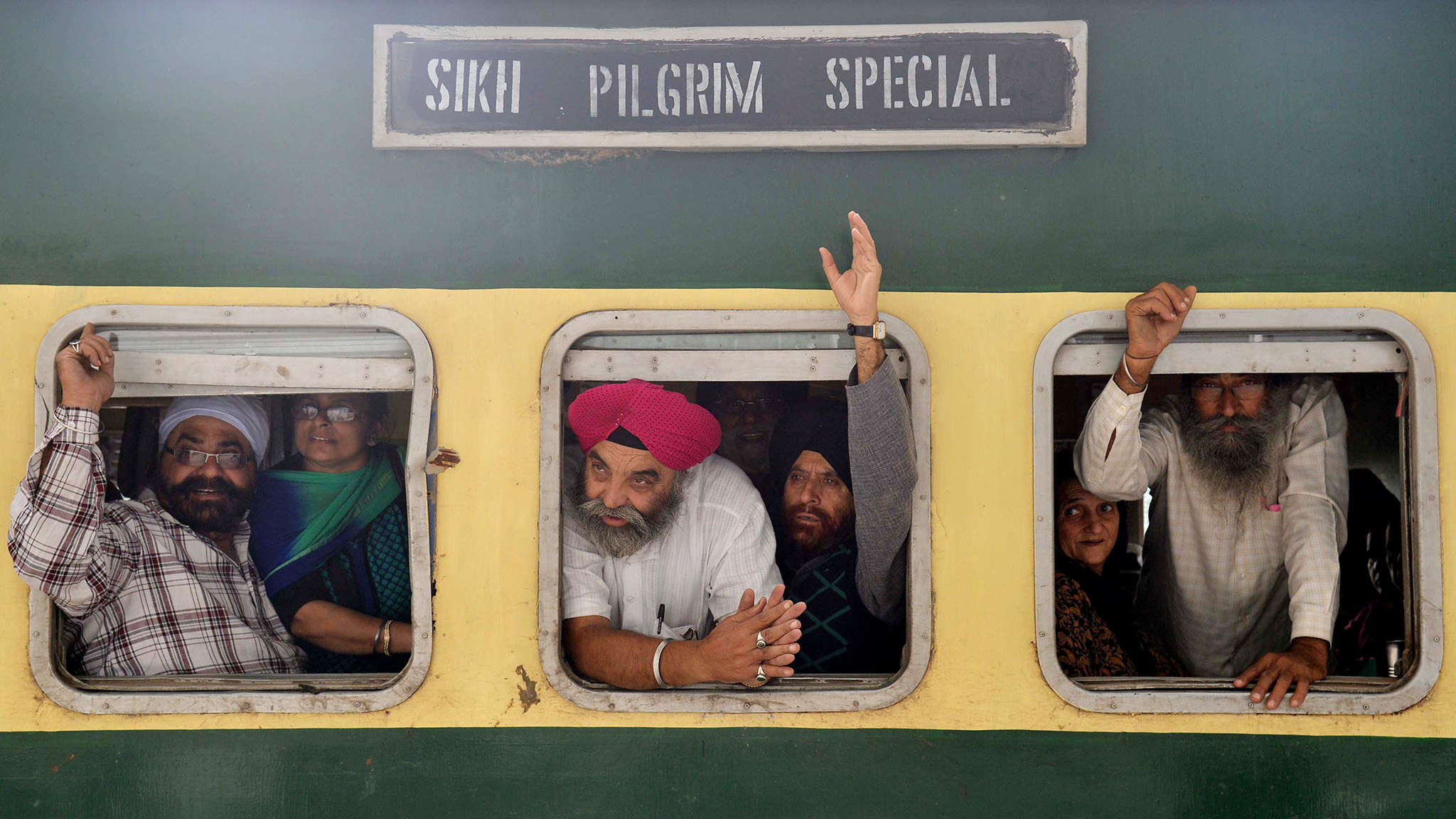 Indian Sikh pilgrims wave from a train bound for Pakistan