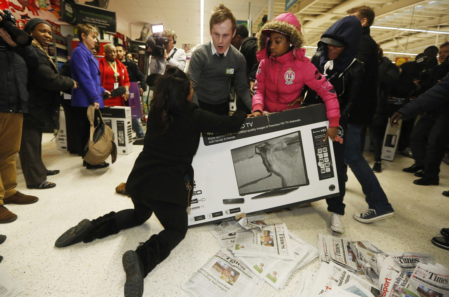 "Shoppers wrestle over a television as they compete to purchase retail items on ""Black Friday"" at an Asda superstore in Wembley"