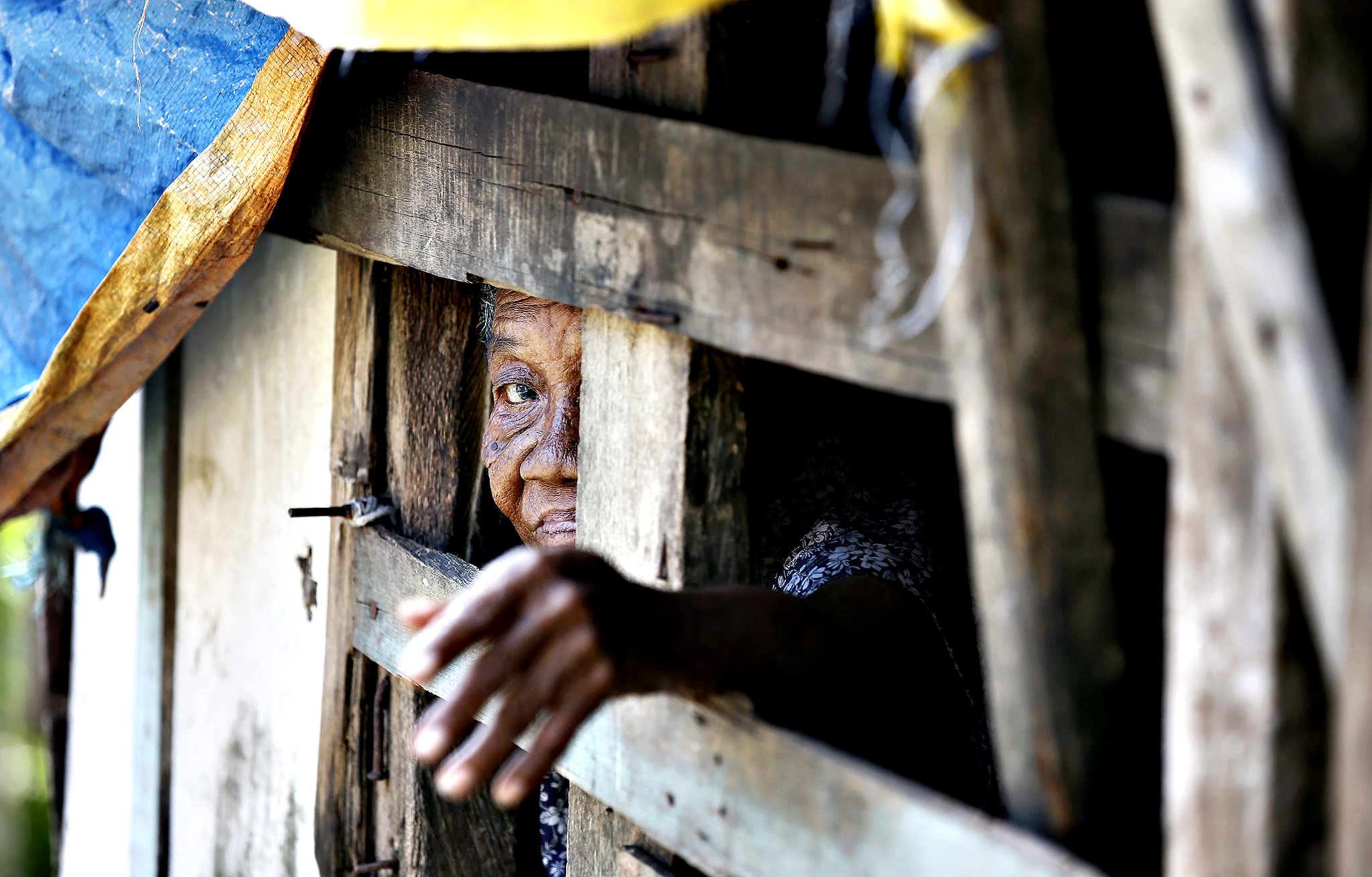 Maring Cahidan, 92, suspected of having a mental illness, sits inside a makeshift cage where she spent the past three months, in Tacloban City, which was damaged by the 2013 Typhoon Haiyan in Leyte province, Philippines, 05 November 2014. One year after Haiyan left nearly 8,000 people dead or missing in the eastern Philippines, many survivors are still suffering from emotional distress despite being busy with physically rebuilding their lives. Over four million people were displaced when Haiyan destroyed or damaged almost everything in its path as it swept through the eastern and central Philippines on 08 November 2013. At least one million of these survivors were residents of coastal communities devastated by tidal surges as high as 10 meters, and are being prioritized for relocation.