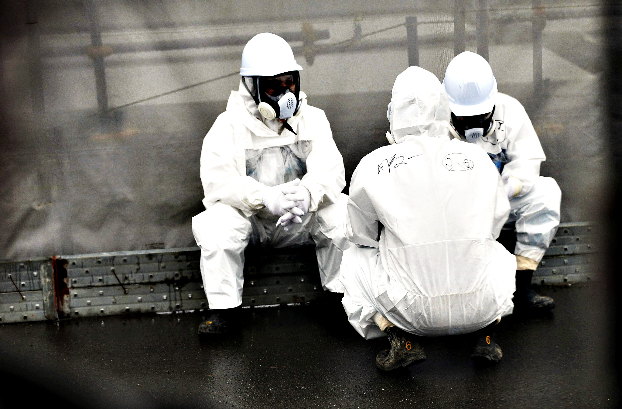 Workers wearing protective gear rest at the Tokyo Electric Power Co. (TEPCO) Fukushima Dai-ichi nuclear power plant, Okuma, Fukushima prefecture, northeastern Japan
