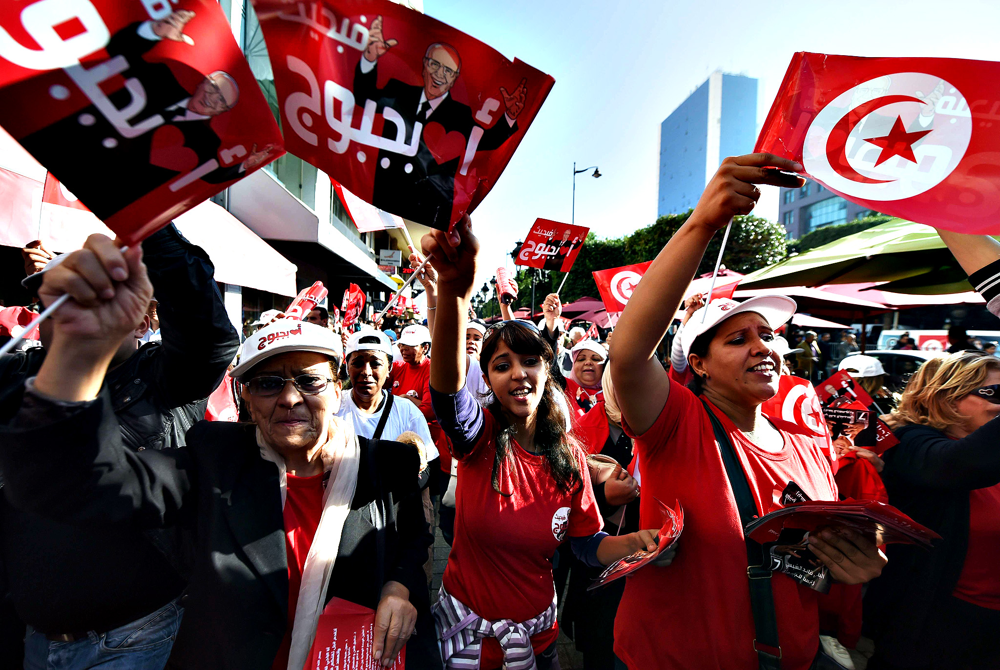Supporters of Tunisian Presidential candidate Beji Caid Essebsi, shout slogans and wave flags on Bourguiba avenue during an election campaign in the capital, Tunis, on November 21, 2014, ahead of the upcoming presidential elections on November 23. Secularist Essebsi is seen as the frontrunner for the elections after his party won milestone parliamentary polls.