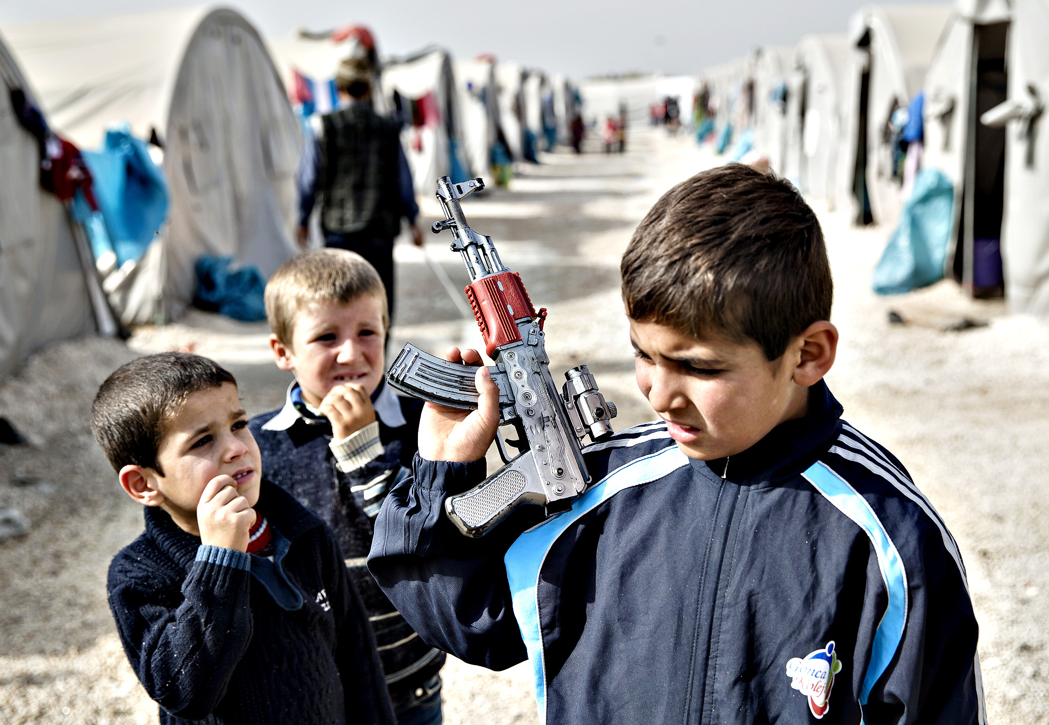 A Syrian Kurdish refugee boy from the Kobani area, holds a toy weapon at a camp in Suruc, on the Turkey-Syria border Thursday, Nov. 13, 2014. Kobani, also known as Ayn Arab, and its surrounding areas, has been under assault by extremists of the Islamic State group since mid-September and is being defended by Kurdish fighters