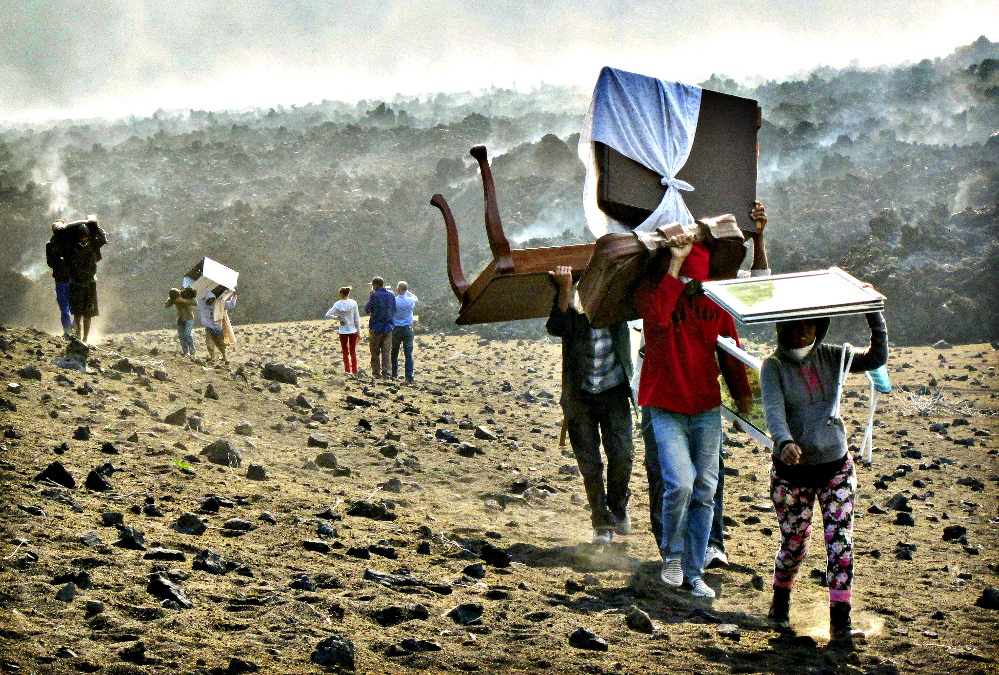 Inhabitants of Cha das Caldeiras carry their belongings as they leave the area due to the activity of the volcano which began erupting in the island of Fogo, Cape Verde, 25 November 2014. The volcano on 23 November 2014 was reported to have erupted at dawn and made it necessary to activate evacuation plans at various points of the island, media reports state. There were no immediate reports yet on any casualties caused by the volcanic eruption.
