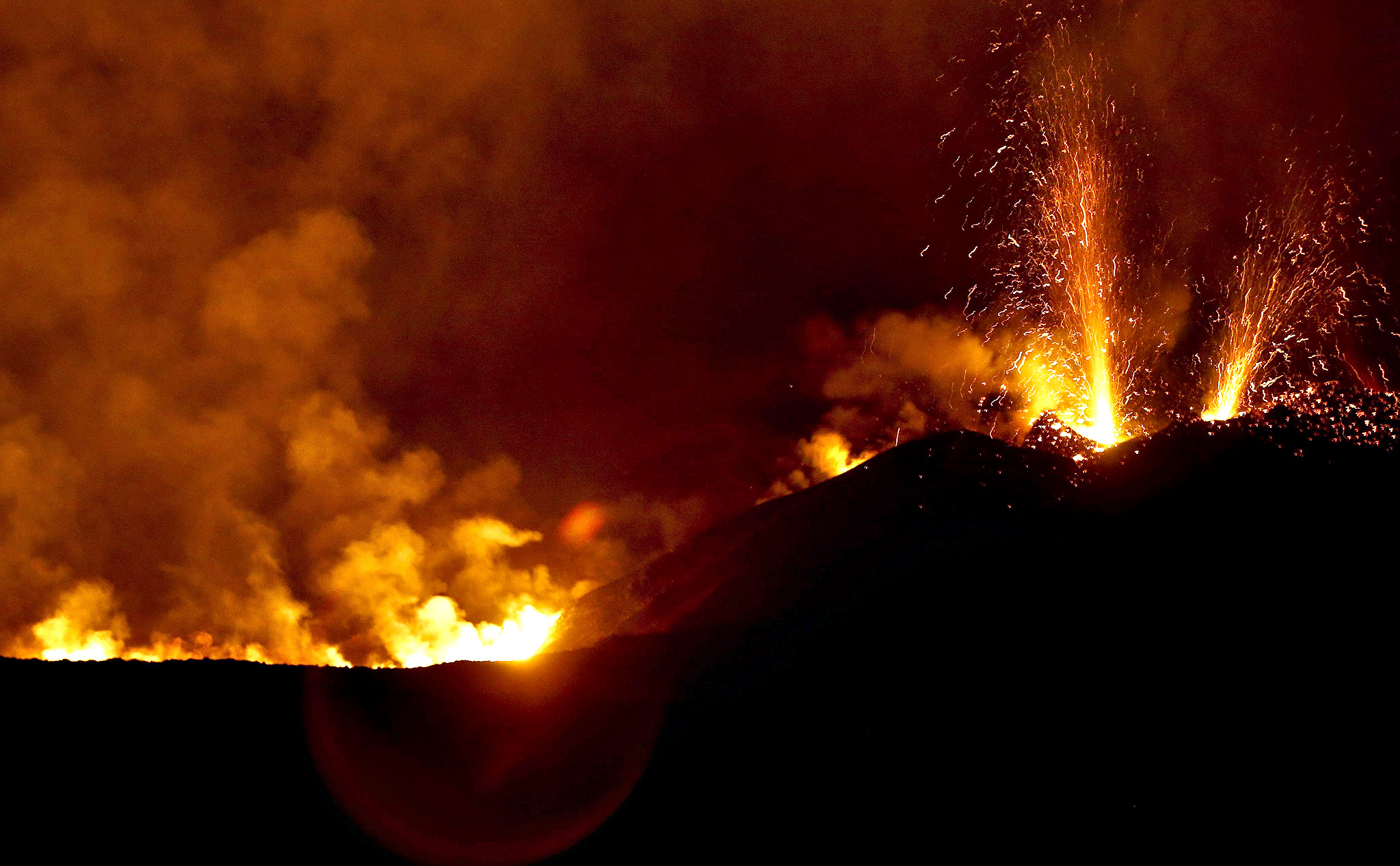 Lava and clouds of smoke and gases being emitted from a volcano on the island of Fogo, Cha das Caldeiras, Cape Verde. After violent explosions recorded at dawn, the volcanic eruption that occurs since 23 November on the Cape Verdean island of Fogo calmed, allowing some inhabitants in the area to recover possession