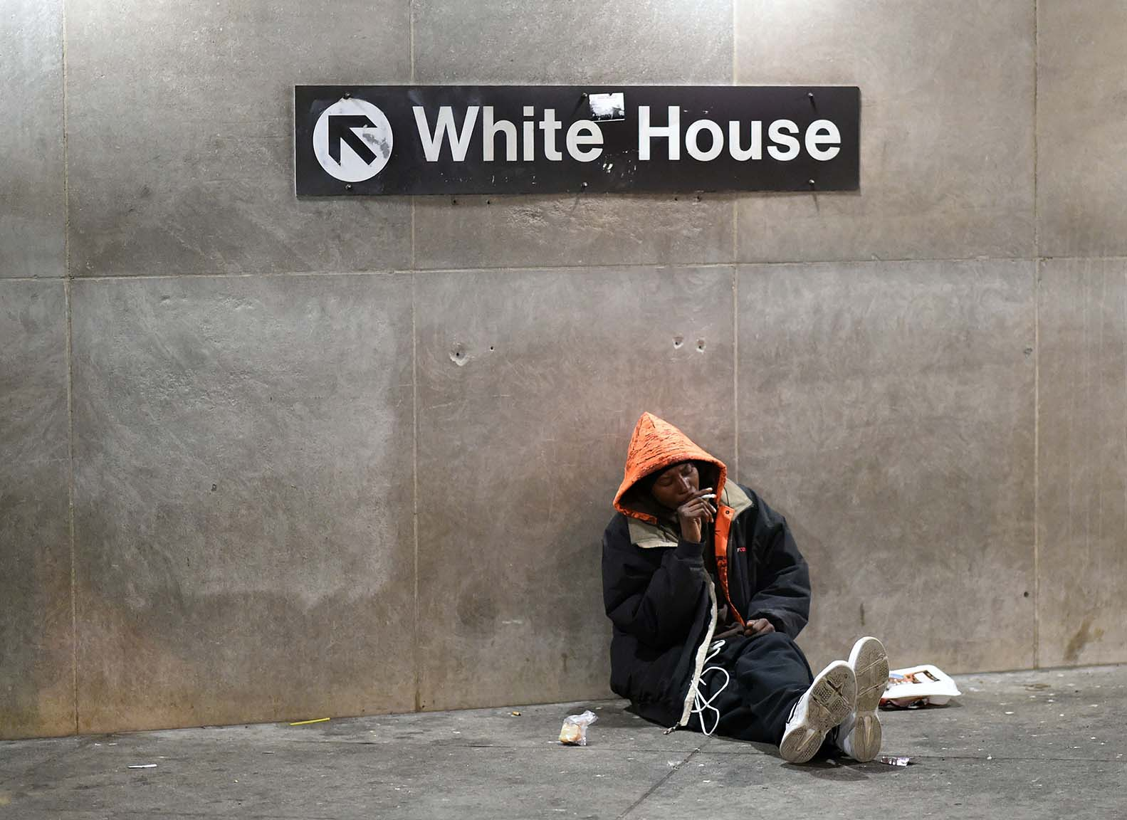 A homeless man sits under a sign giving directions to the White House