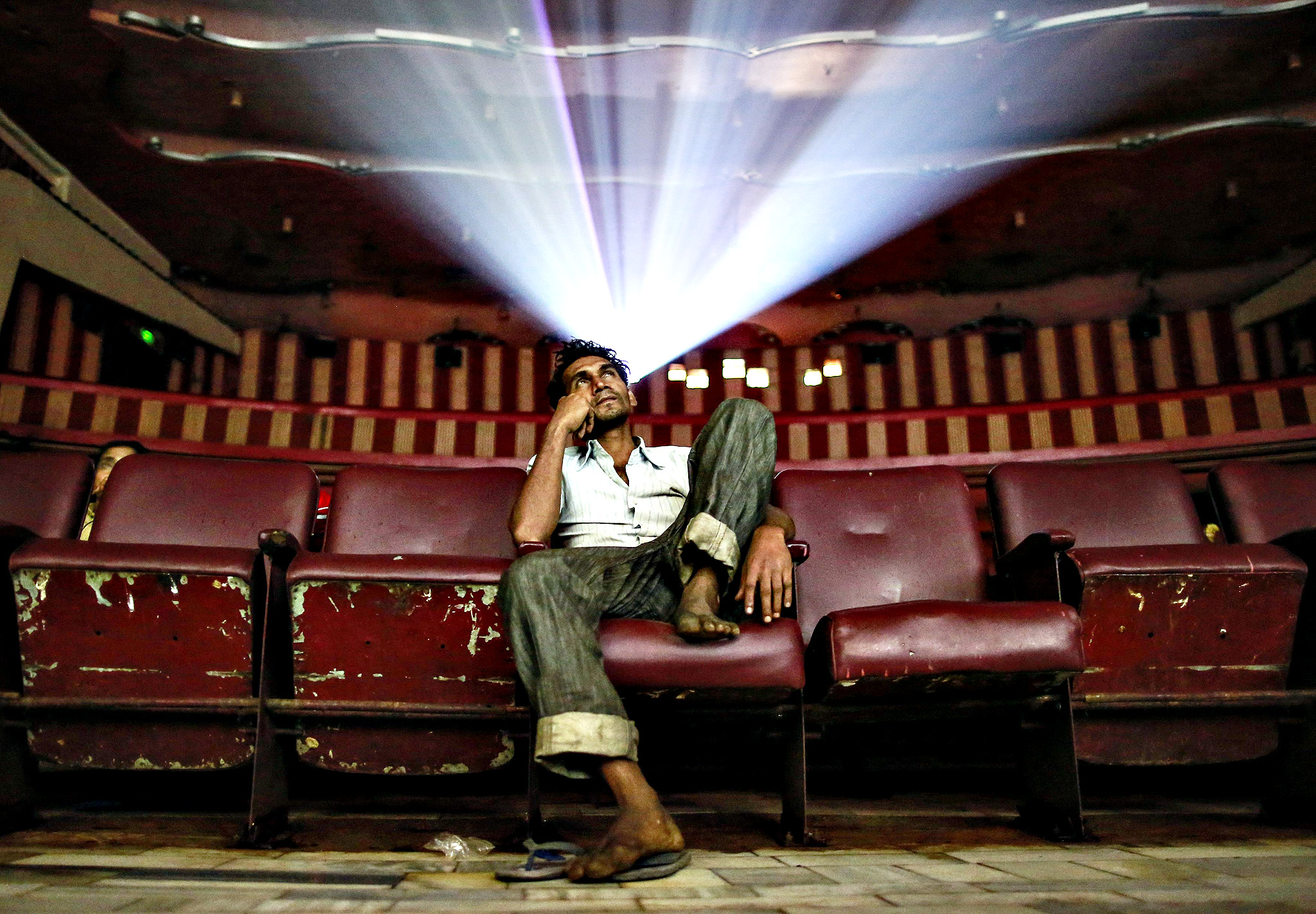 "A cinema goer watches Bollywood movie ""Dilwale Dulhania Le Jayenge"" (The Big Hearted Will Take the Bride), starring actor Shah Rukh Khan, inside Maratha Mandir theatre in Mumbai December 11, 2014. The movie, released in October 1995, has set a record of completing 1000 weeks of continuous screening at a cinema, a feat unmatched by any other Bollywood movies. According to Manoj Desai, owner of the theatre, the movie, which is still being screened, enjoys at least 50 to 60 percent occupancy on weekdays and full house on weekends at his theatre. The movie is screened only in the morning and the ticket price ranges from 15 to 20 Indian rupees ($0.24-$0.32). Picture taken December 11, 2014."