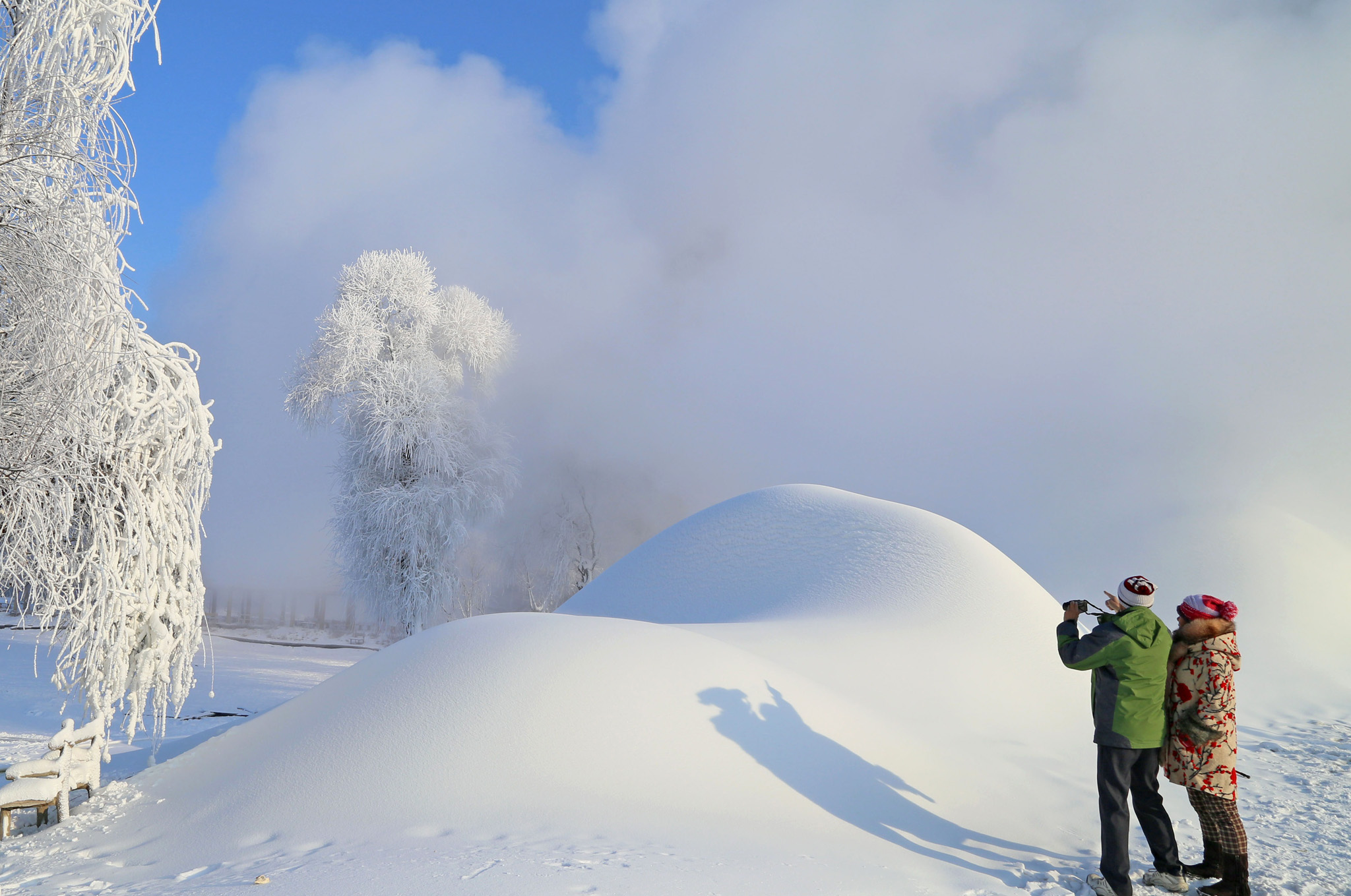 Residents take photos of snow-covered trees in Jilin, in northeast China's Jilin provinc