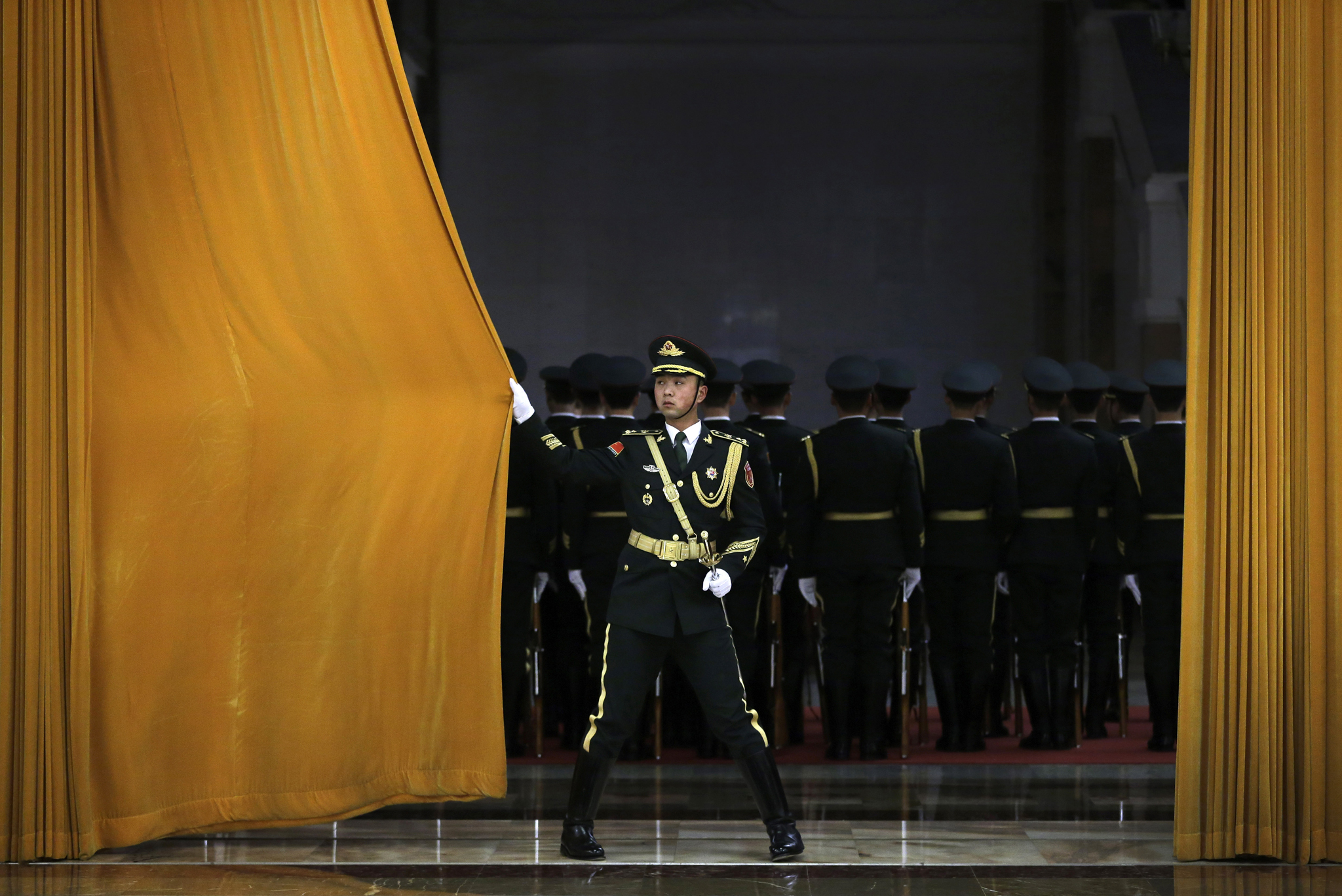 A Chinese People's Liberation Army soldier closes a curtain after members of honor guard rehearse for a welcome ceremony held by Chinese President Xi Jinping for visiting Egyptian President Abdel-Fattah el-Sissi at the Great Hall of the People in Beijing, China Tuesday, Dec. 23, 2014
