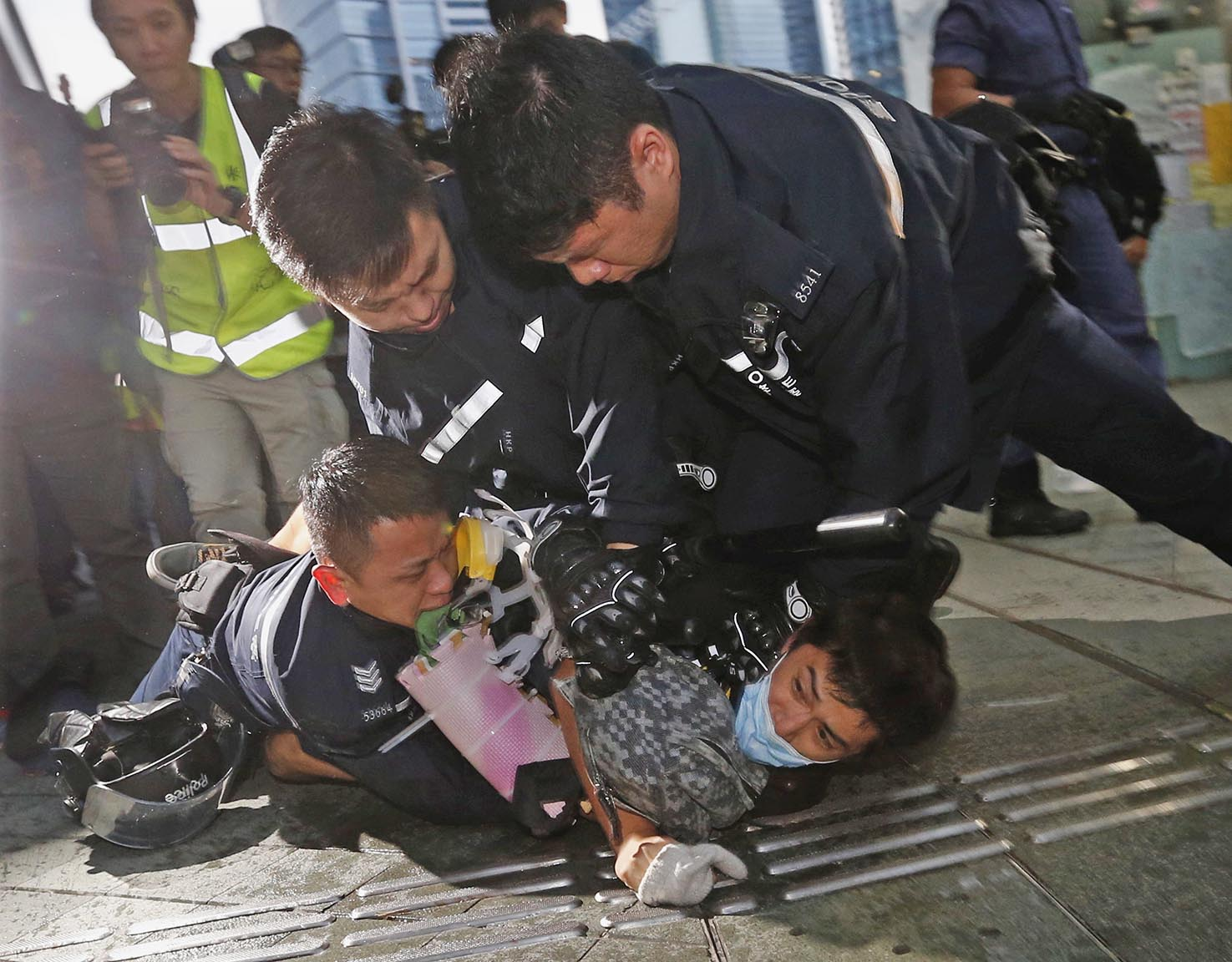Pro-democracy protester and a policeman fall to the ground as two other policemen detain protester during clashes outside the government headquarters in Hong Kong