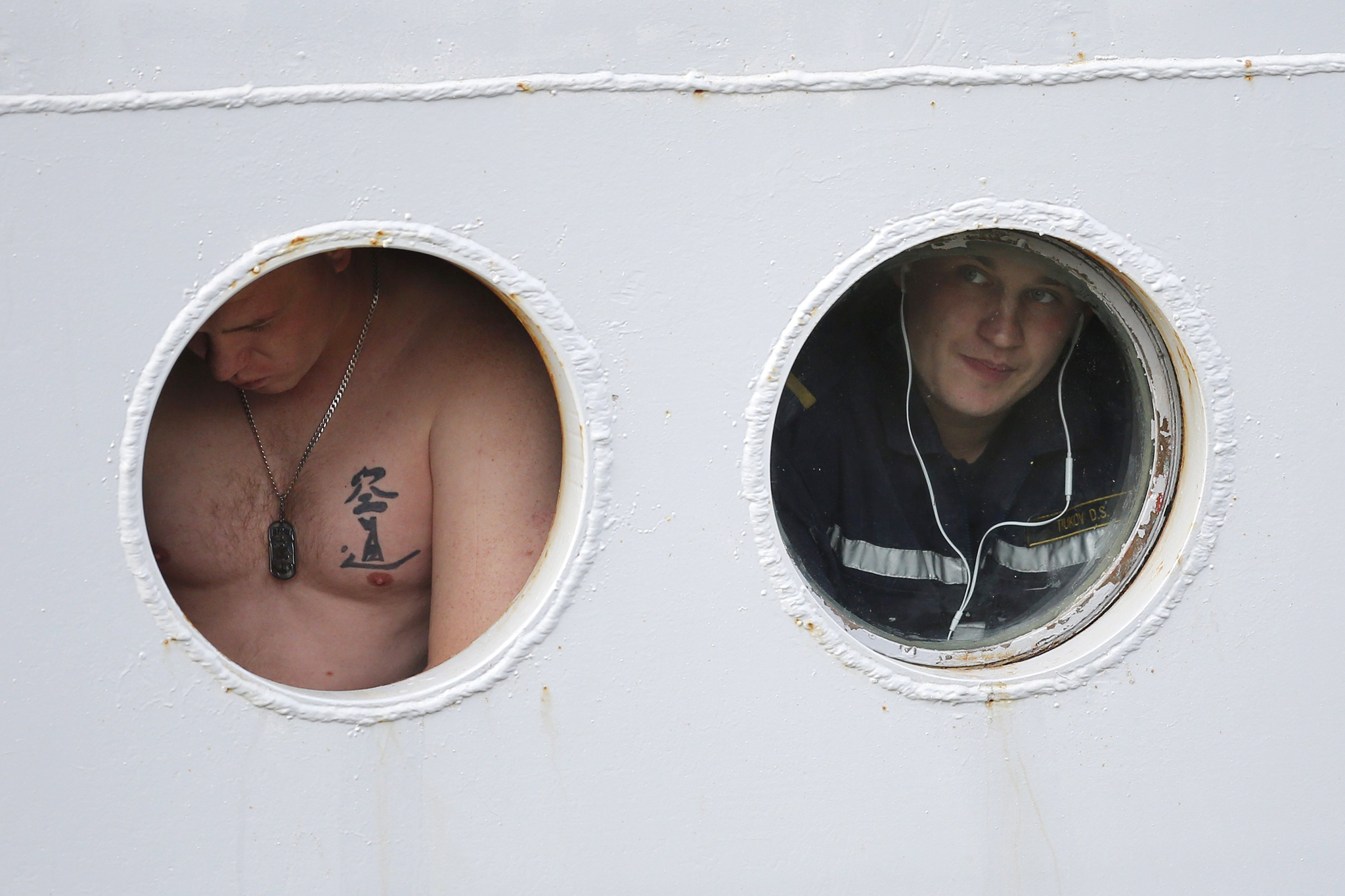 A Russian sailor looks through a porthole of the Russian Navy frigate Smolny as the ship leaves the STX Les Chantiers de l'Atlantique shipyard site in Saint-Nazaire...A Russian sailor looks through a porthole of the Russian Navy frigate Smolny as the ship leaves the STX Les Chantiers de l'Atlantique shipyard site in Saint-Nazaire, western France, December 18, 2014. A ship carrying the Russian sailors, who have been training for months on a French-built Mistral helicopter carrier, left the French port of Saint-Nazaire on Thursday, with it still unclear whether Paris will finally deliver the ship to Moscow. The sailors arrived in late June at the shipyard to begin training on a first carrier, named Vladivostock, which France was due to deliver to Russia by the last quarter of 2014. REUTERS/Stephane Mahe (FRANCE - Tags: BUSINESS MILITARY POLITICS)