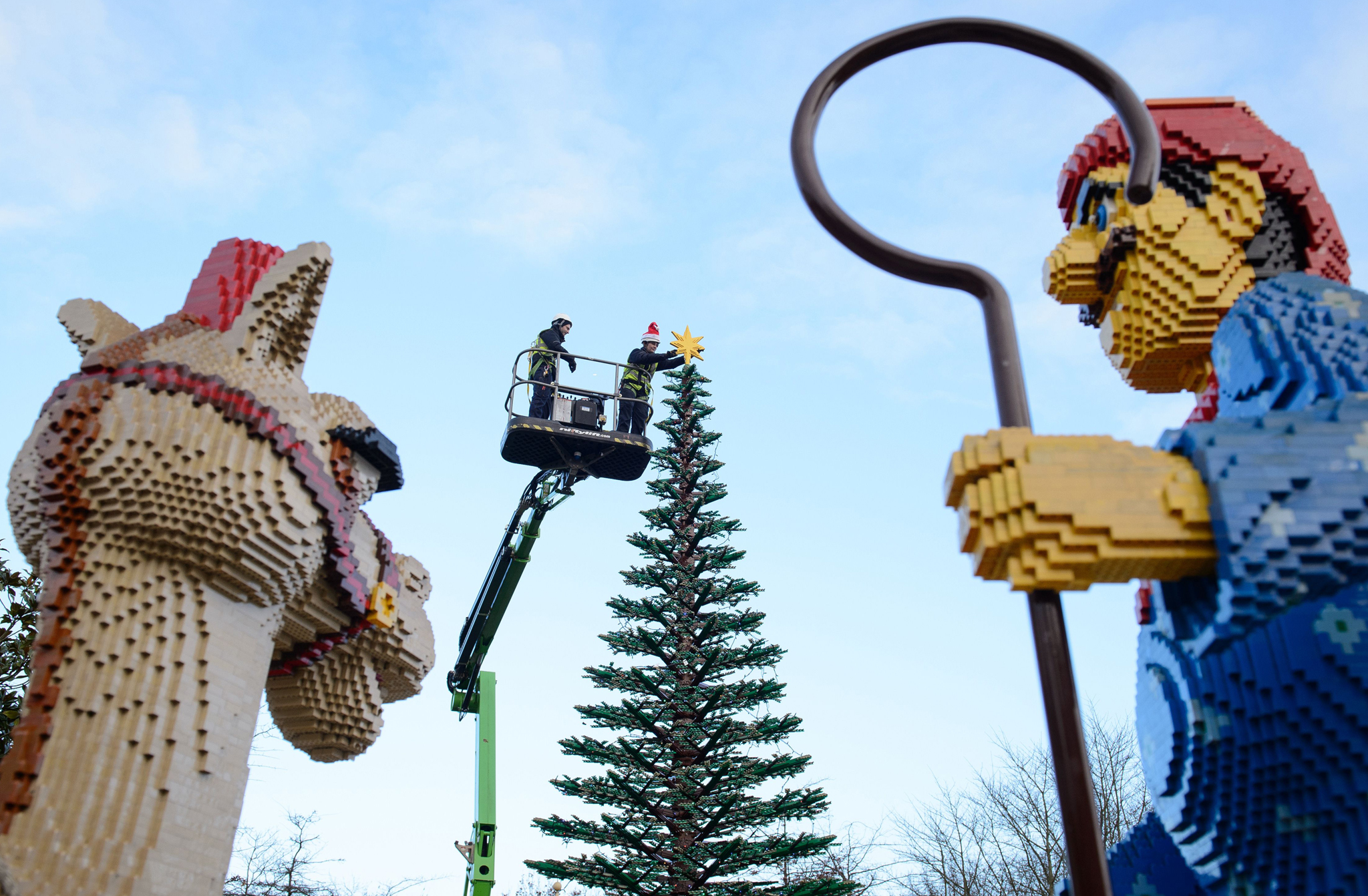 Legoland model maker Katrina James (R) poses with a 3kg Lego star as she places it onto the top of a 8m tall Lego christmas tree at Legoland Windsor Resort, west of London. The tree is comprised of 300,000 lego bricks and took 4 weeks to build.