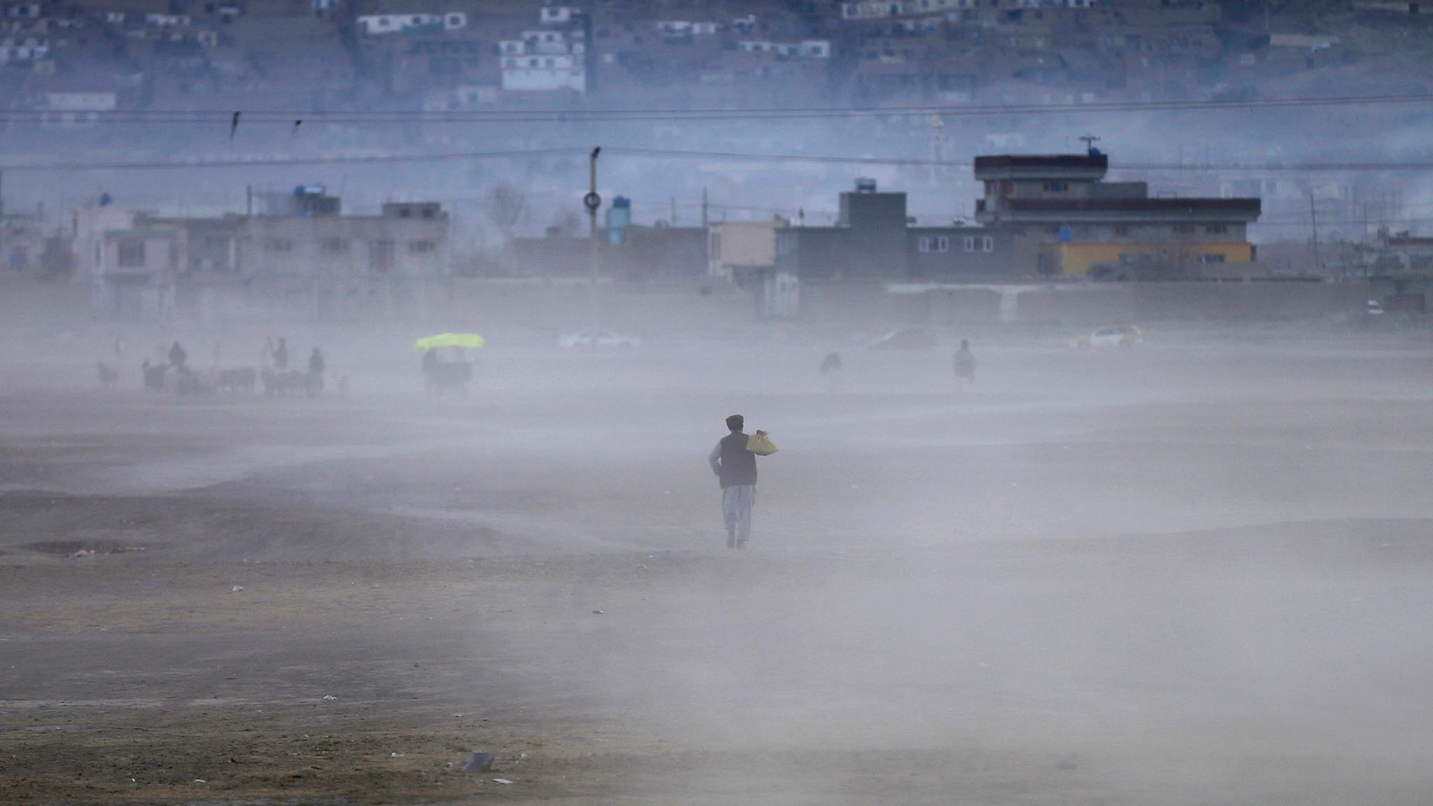 An Afghan man heads home walking through a dust cloud as the sun sets in Kabul
