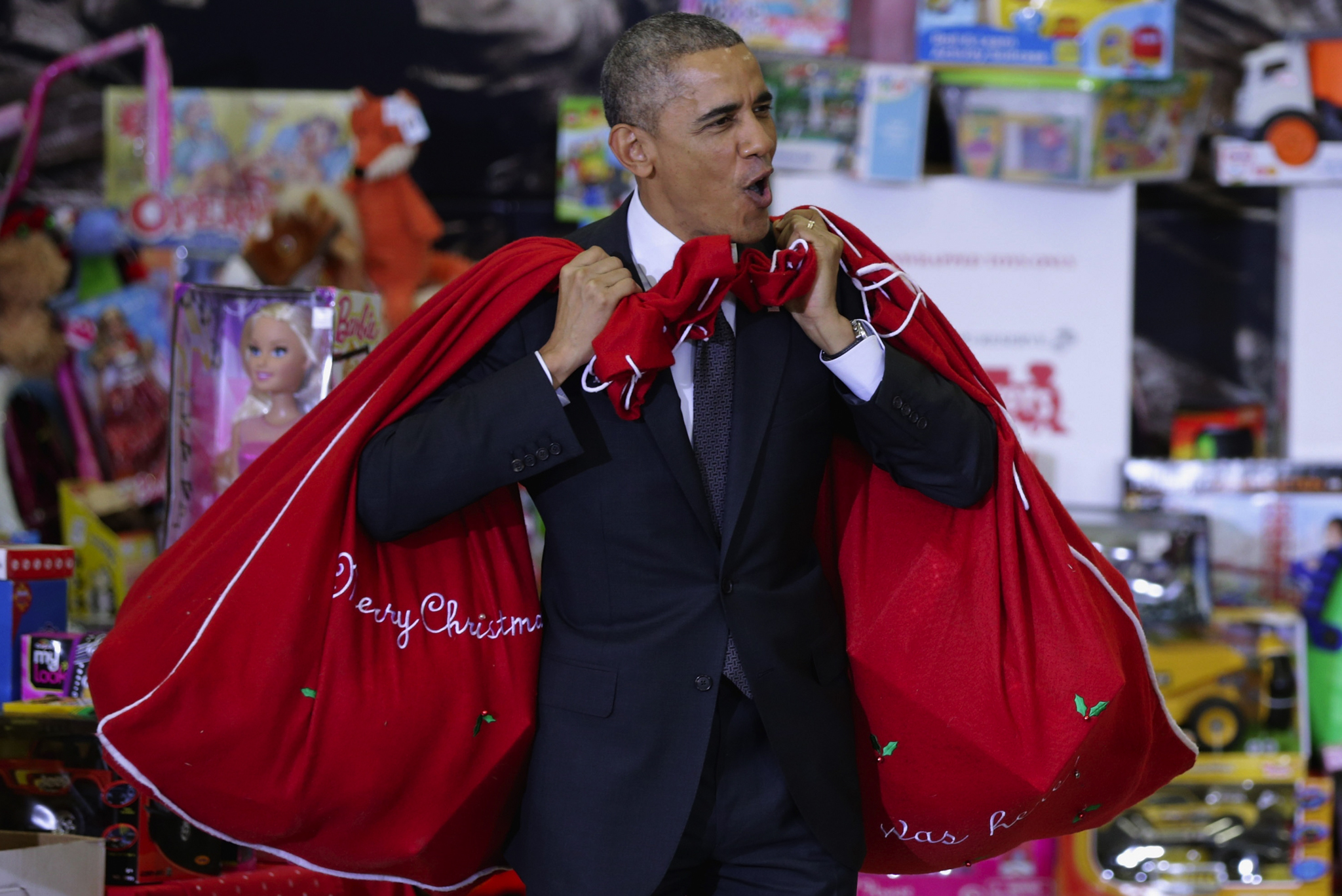 U.S. President Barack Obama, with bags slung over his shoulders, delivers toys and gifts donated by Executive Office of the President staff to the Marine Corps Reserve Toys for Tots Program at Joint Base Anacostia-Bolling.