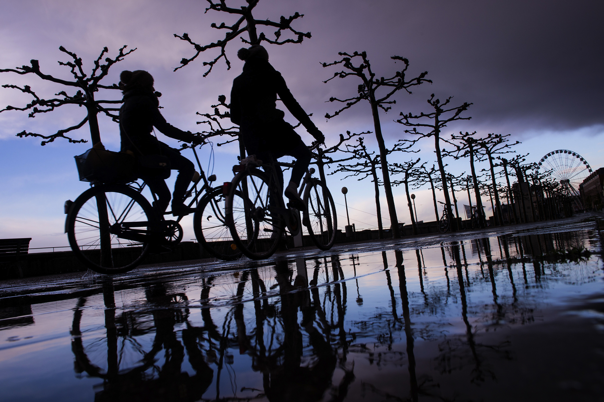 Two cyclists are reflected in a puddle shortly after a storm on the banks of the river Rhine in Duesseldorf, Germany.
