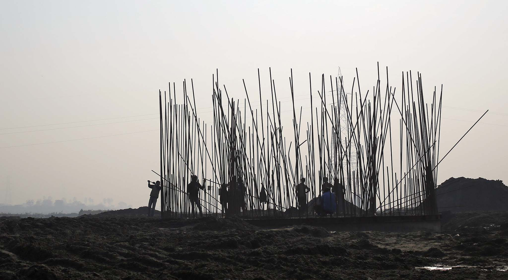 Labourers work at the construction site of a bridge being built over the river Yamuna for metro rail in New Delhi