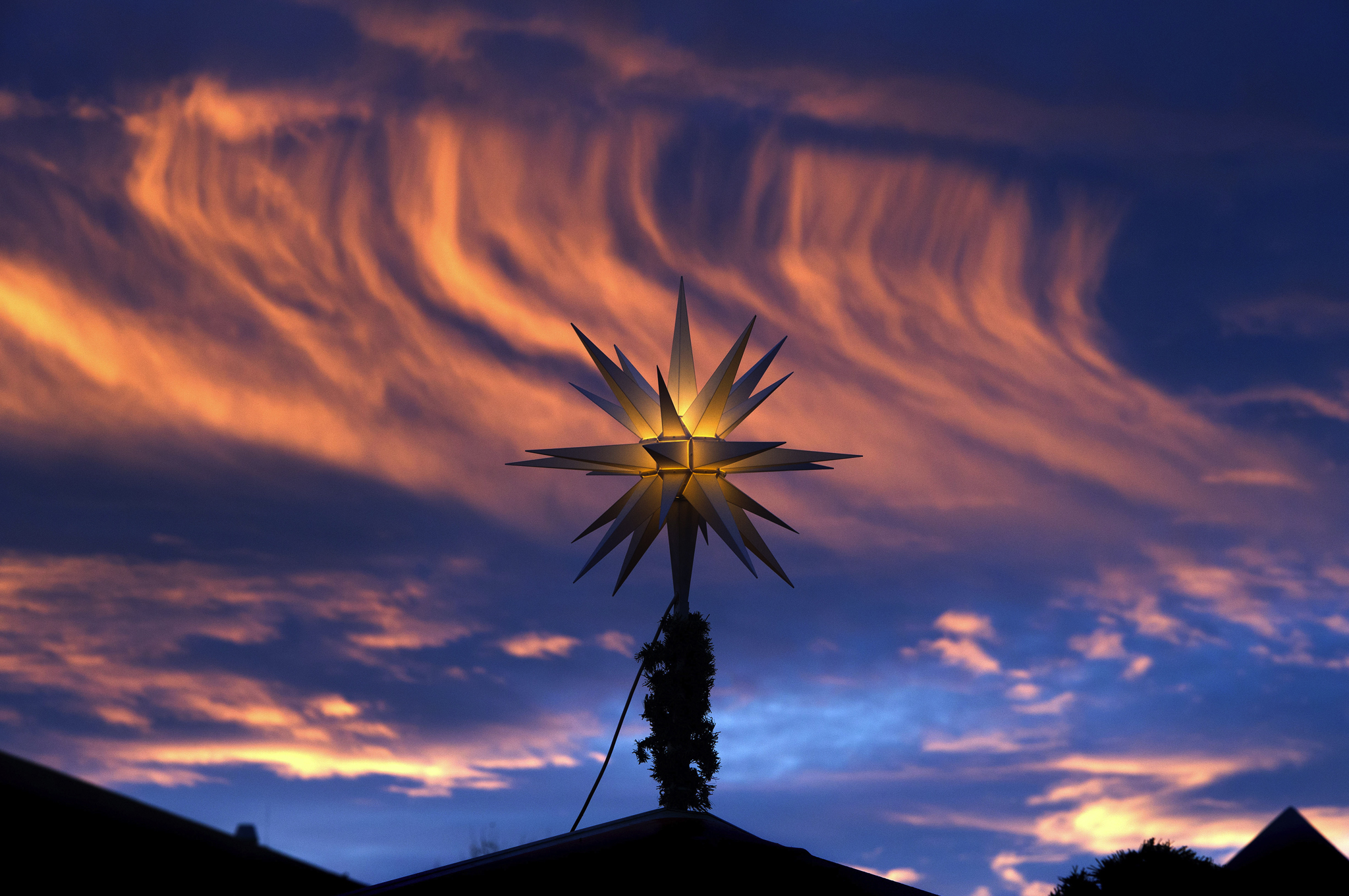 A Christmas star on top of a sales booth is pictured against the colorful morning sky at the Christmas market in Dresden, eastern Germany.