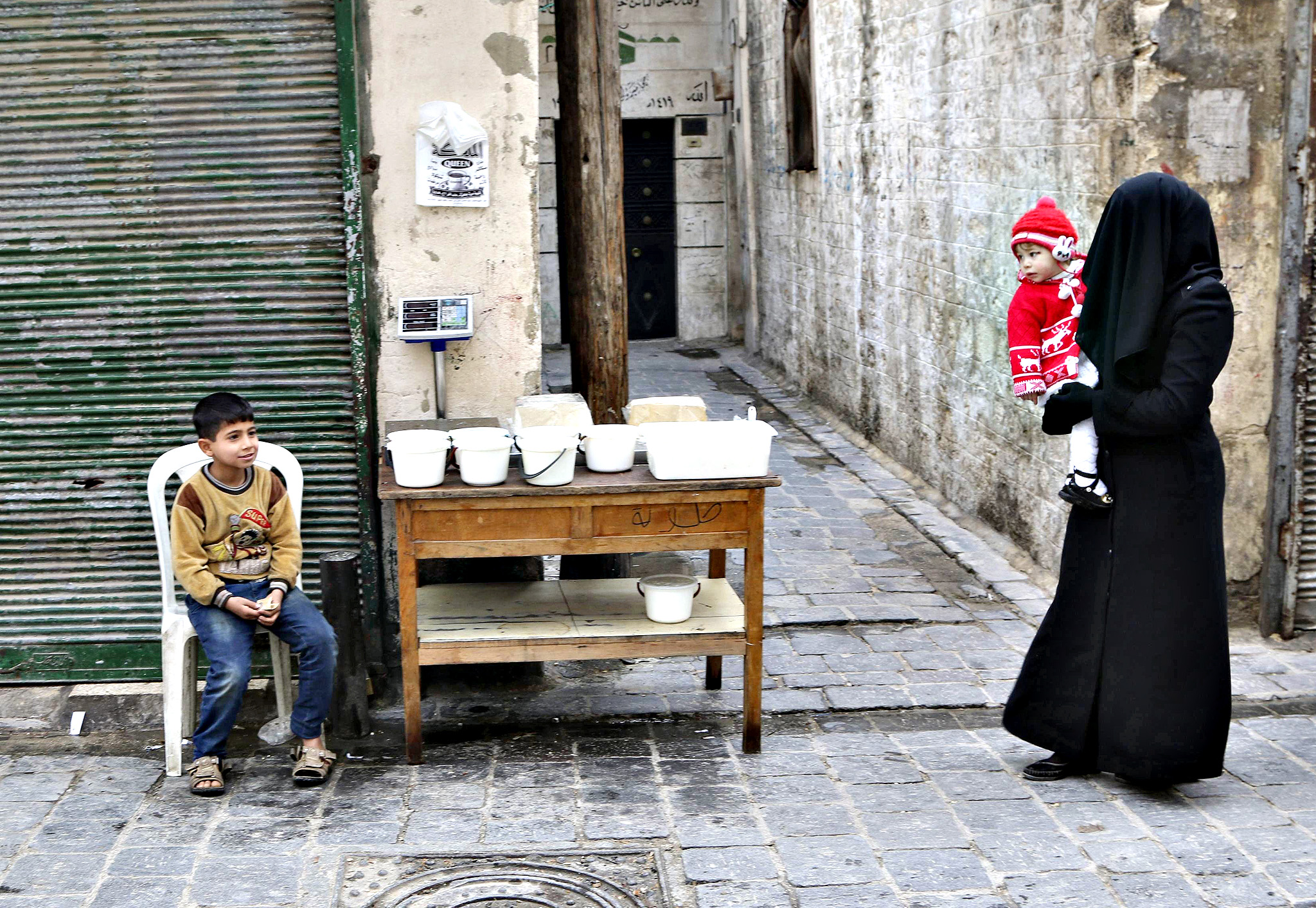 A woman carries a child as she walks past a boy selling yogurt along a street in Aleppo's Bab al-Hadeed district December 10, 2014.