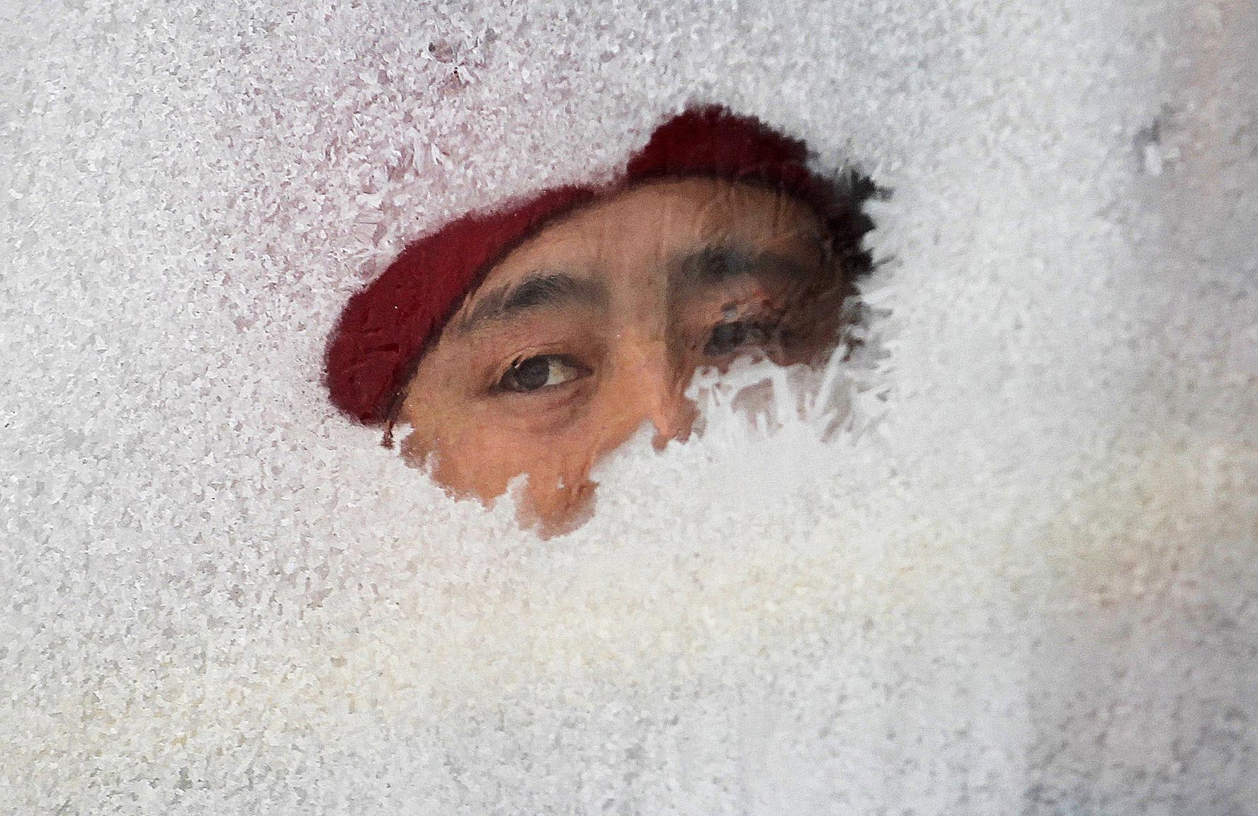 A woman looks out from a window of a bus covered with frost in Changchun, Jilin province