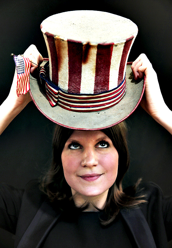 An auction house worker wears a hand-painted 'Uncle Sam' top hat owed and worn by Grateful Dead rock group's Jerry Garcia,  as she poses for the photographers, in London, Friday, Dec. 12, 2014.The bi-annual 20/21 Pop Culture sale scheduled for Dec. 16, 2014, will present music and film aficionados with memorabilia associated with legends of rock, pop and Hollywood, according to Christie's auction house.