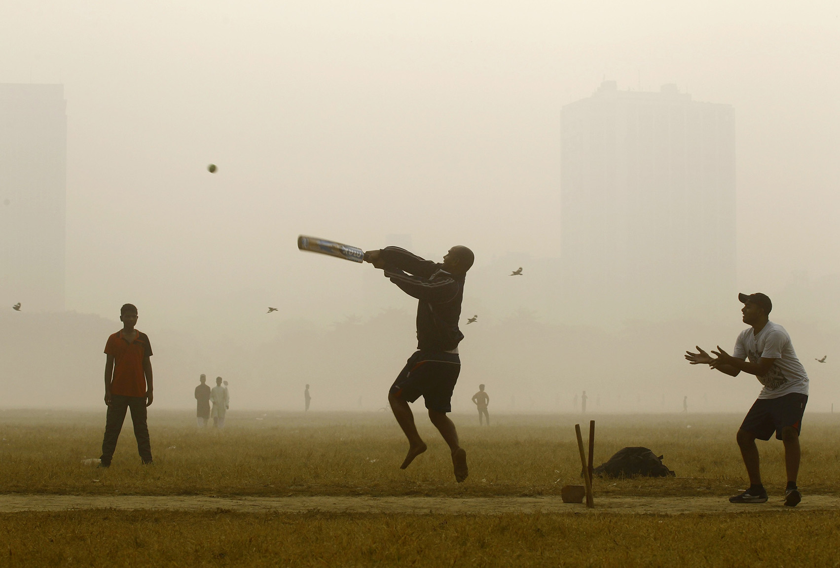 Men play cricket in a public park on a foggy morning in Kolkata