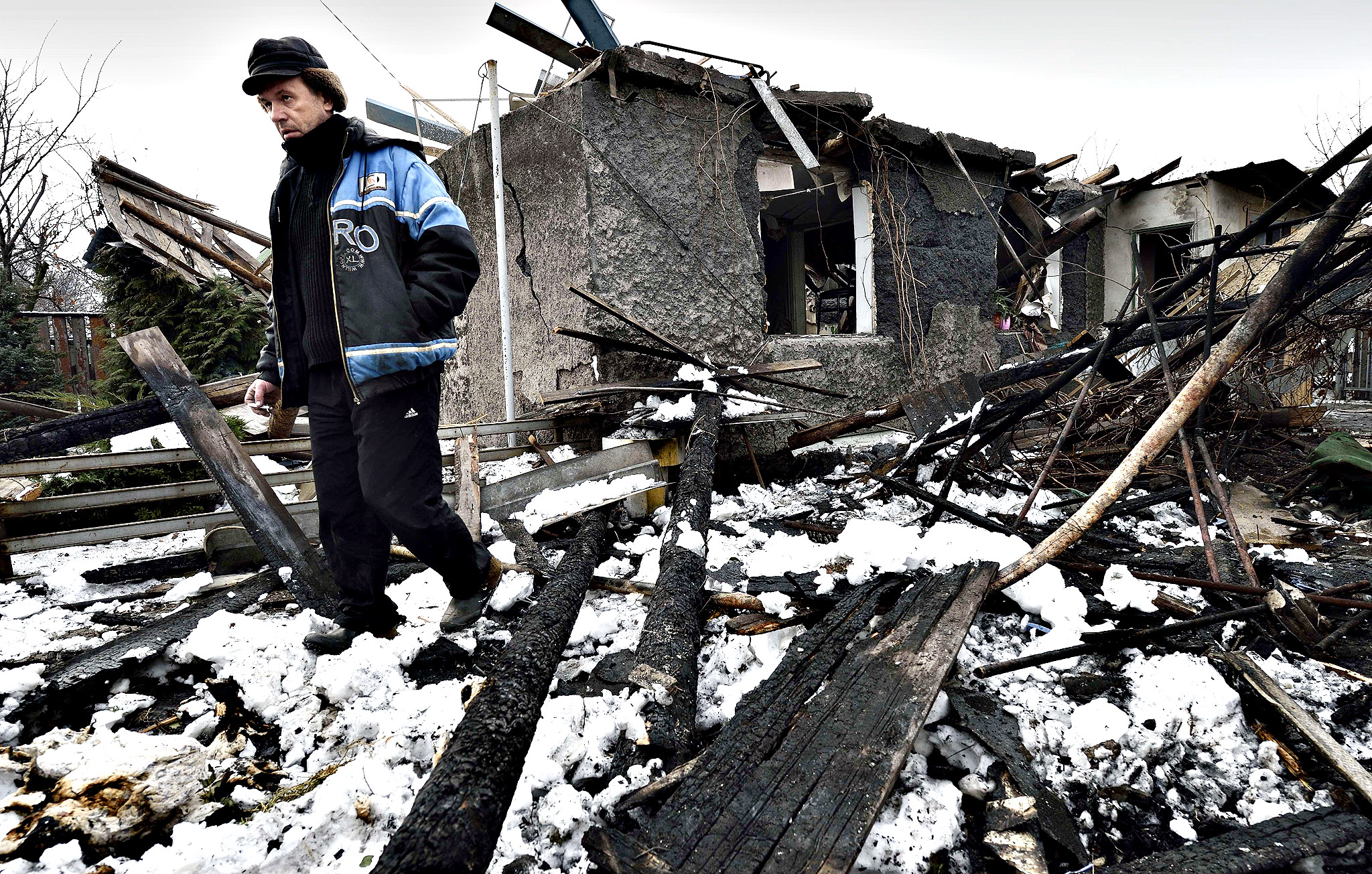 "A man stands next to his house destroyed overnight by shelling in the Kuibishevskiy district of the eastern Ukrainian city of Donetsk , controlled by pro-russian fighters, on December 9, 2014. Ukrainian President Petro Poroshenko said on December 9 a ceasefire along the front line in the east of his country appeared to be holding after Kiev declared a ""day of silence"" in the war with pro-Russian separatists."
