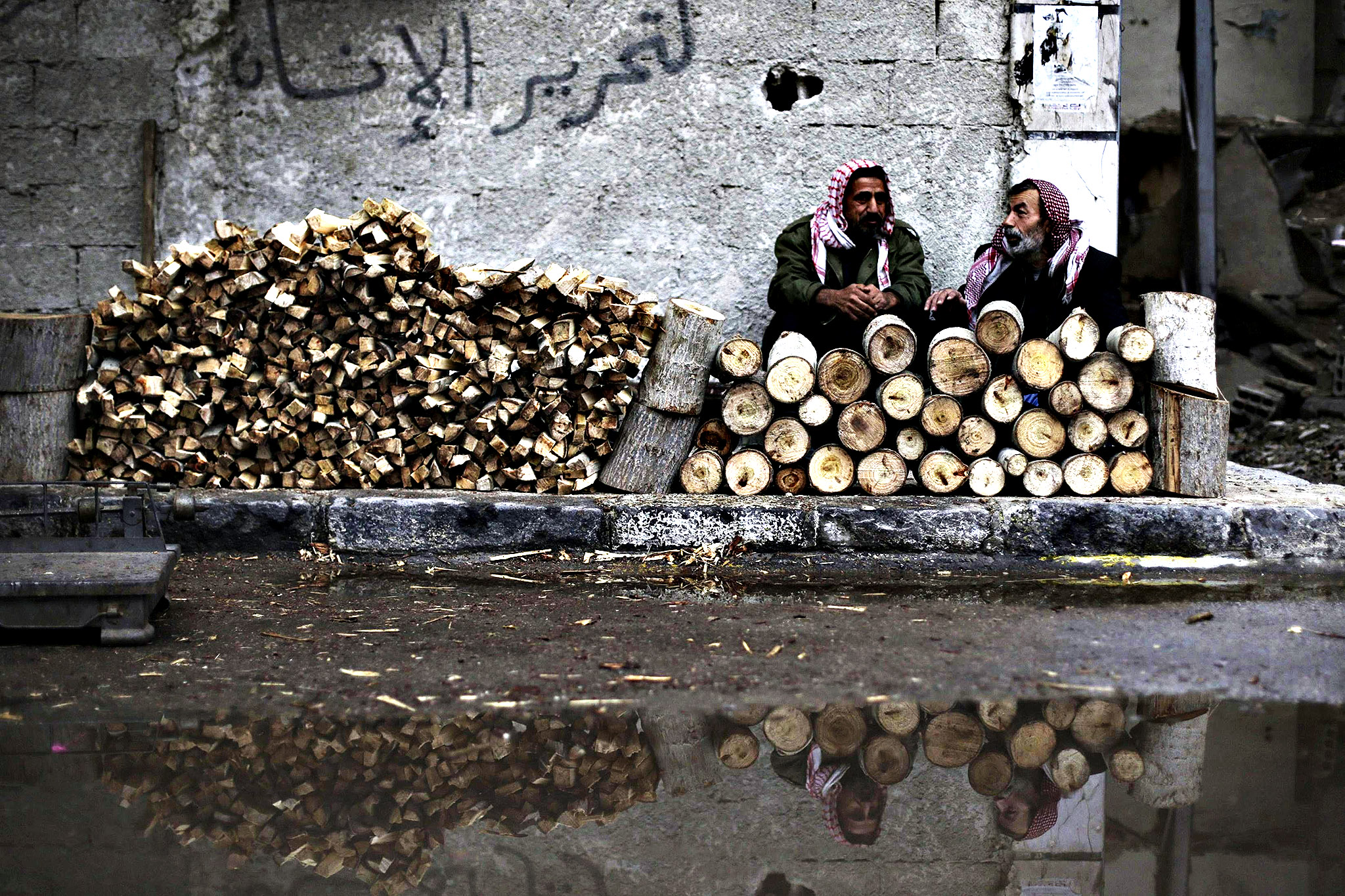 "Men sell firewood on a rainy day in the Duma neighbourhood of Damascus December 9, 2014. The graffiti on the wall reads, ""For the liberation of the humans""."