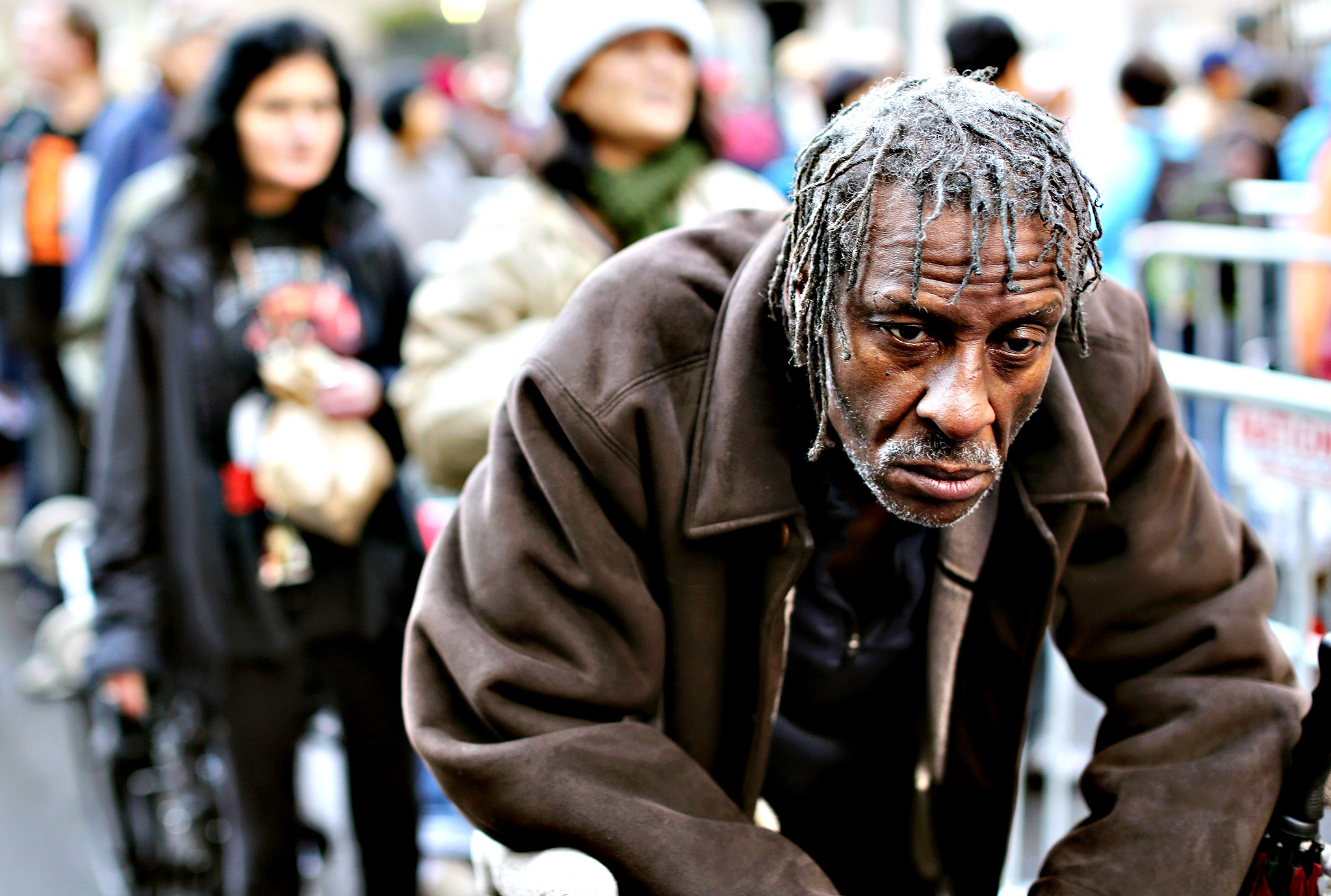 A man waits in line for one of 5,000 holiday food bags provided at Glide Memorial Church in the Tenderloin neighborhood in San Francisco, California December 17, 2014. Glide's foundation serves a cross-section of homeless and low-income people, and provides a variety of services including free meals.