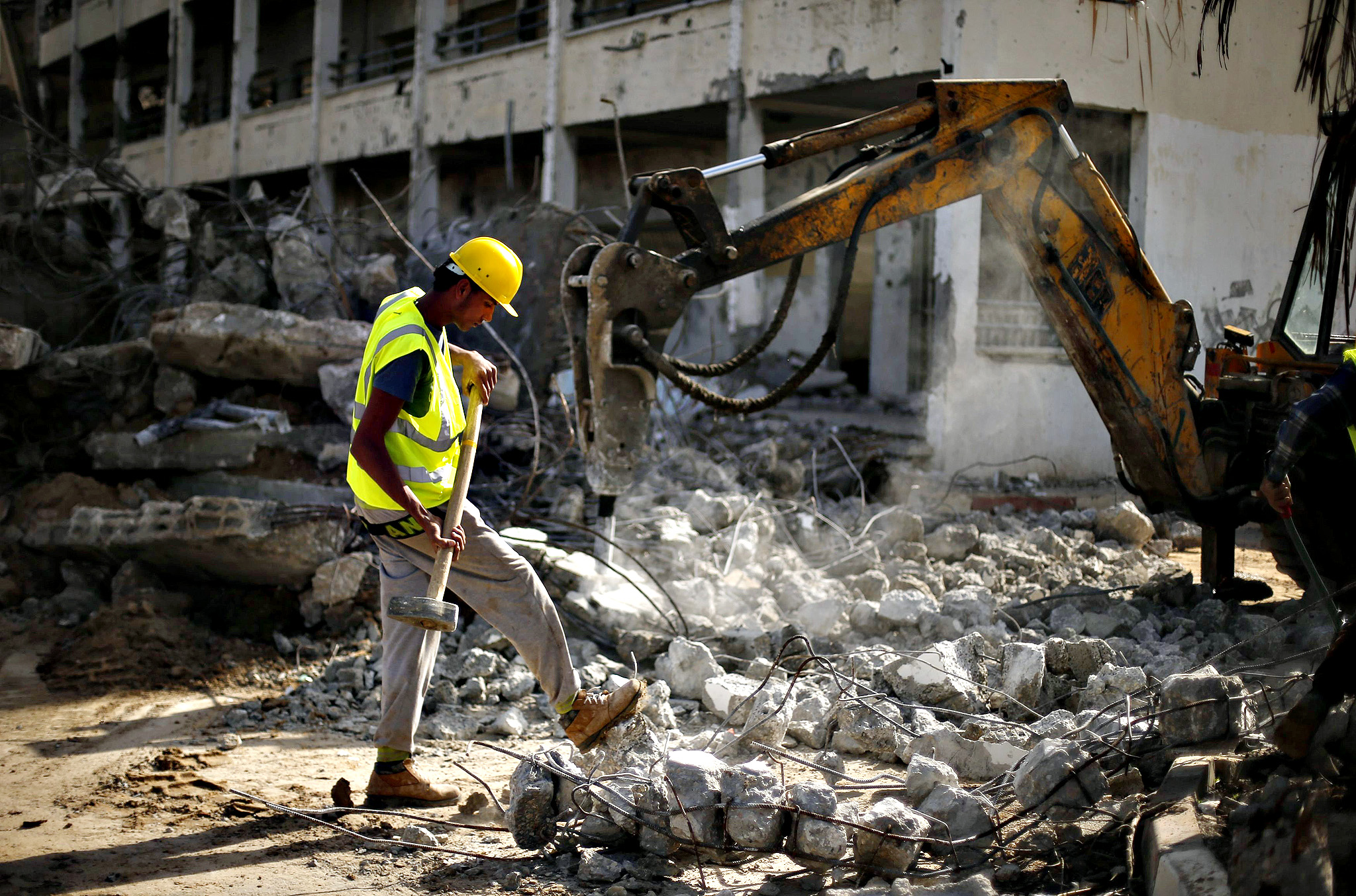 A Palestinian worker carries a hammer as he participates in efforts to clear the rubble of a school, that witnesses said was destroyed by Israeli shelling during the most recent conflict between Israel and Hamas, in the east of Gaza City December 3, 2014. According to housing minister Mufeed al-Hasayna, Gaza needs 8,000 tonnes of cement a day to meet demand. A new system set up with the United Nations to comply with Israeli requirements lets through at most 2,000, he said. At that rate, reconstruction would take more than 30 years, said Hasayna, one of four members of the unity government based in Gaza rather than the West Bank. Hasayna signed an agreement with the U.N. Development Programme and the Swedish government last week to equip and hire local contractors to clear and recycle rubble from northern Gaza