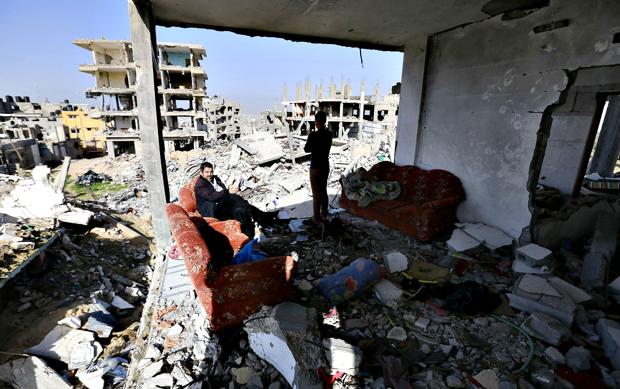 A Palestinian man and his son are seen in the living room of their house which was destroyed during the 50-day Gaza war between Israel and Hamas-led militants, on Decembre 10, 2014 in Gaza City. The Israeli military committed war crimes during its Gaza offensive this summer and must be investigated, human rights monitor Amnesty International yesterday.
