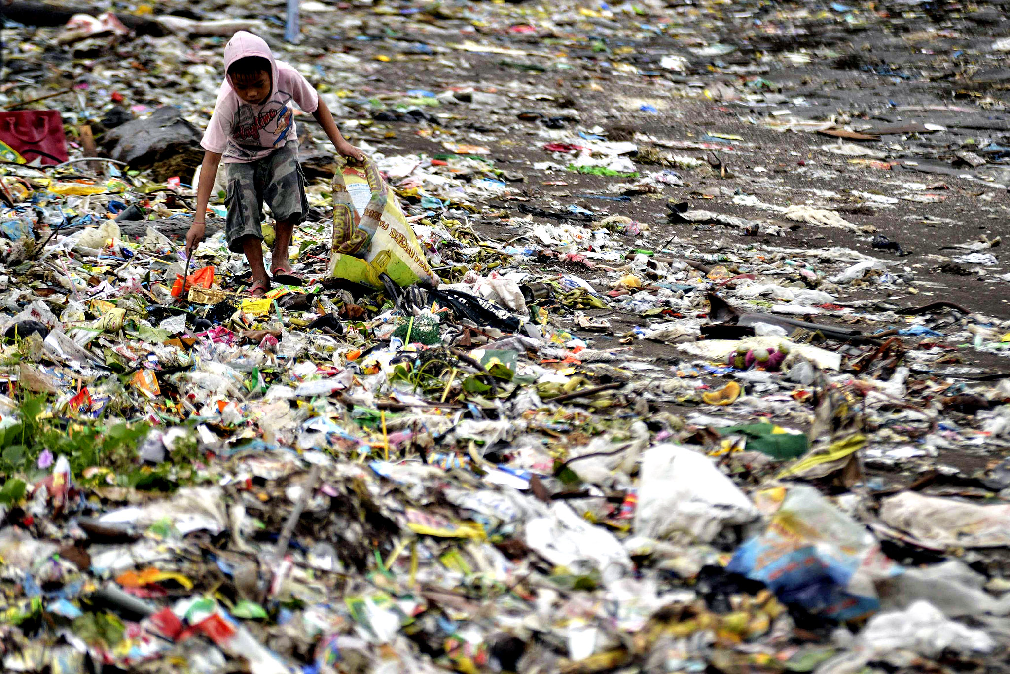 A boy looks for recyclable materials among the garbage washed ashore due to Typhoon Hagupit in Cavite, south of Manila December 9, 2014. Typhoon Hagupit weakened further on Tuesday as the storm crawled across the central Philippines, while rescue workers struggled in its aftermath to reach towns in central provinces where thousands of homes were wrecked and at least 27 people killed