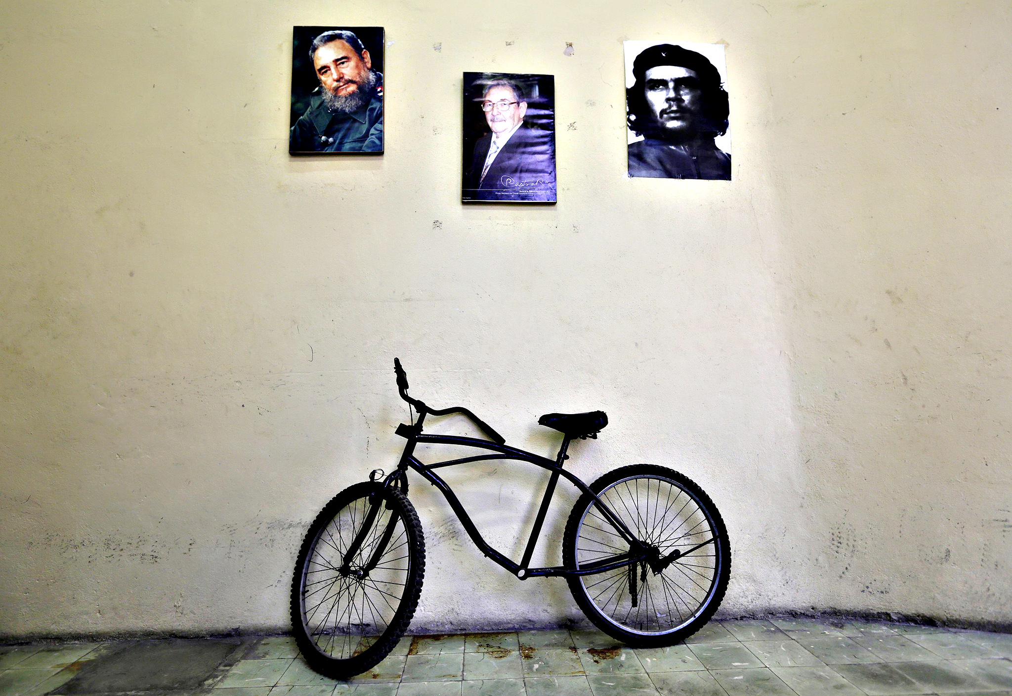 A bicycle is parked under pictures of Cuba's former president Fidel Castro, Raul Castro, brother of Fidel and Cuba's president, and revolutionary hero Ernesto 'Che' Guevara (L-R) in an office in Havana December 19, 2014. With Washington agreeing to restore full diplomatic ties that were cut in the early 1960s, Cuba's communist government may not be able to blame its old Cold War nemesis so readily. Cuba has repeatedly sought to dispel the idea that it secretly wanted the embargo in place, saying if the Americans believed that they should challenge Cuba by lifting it.