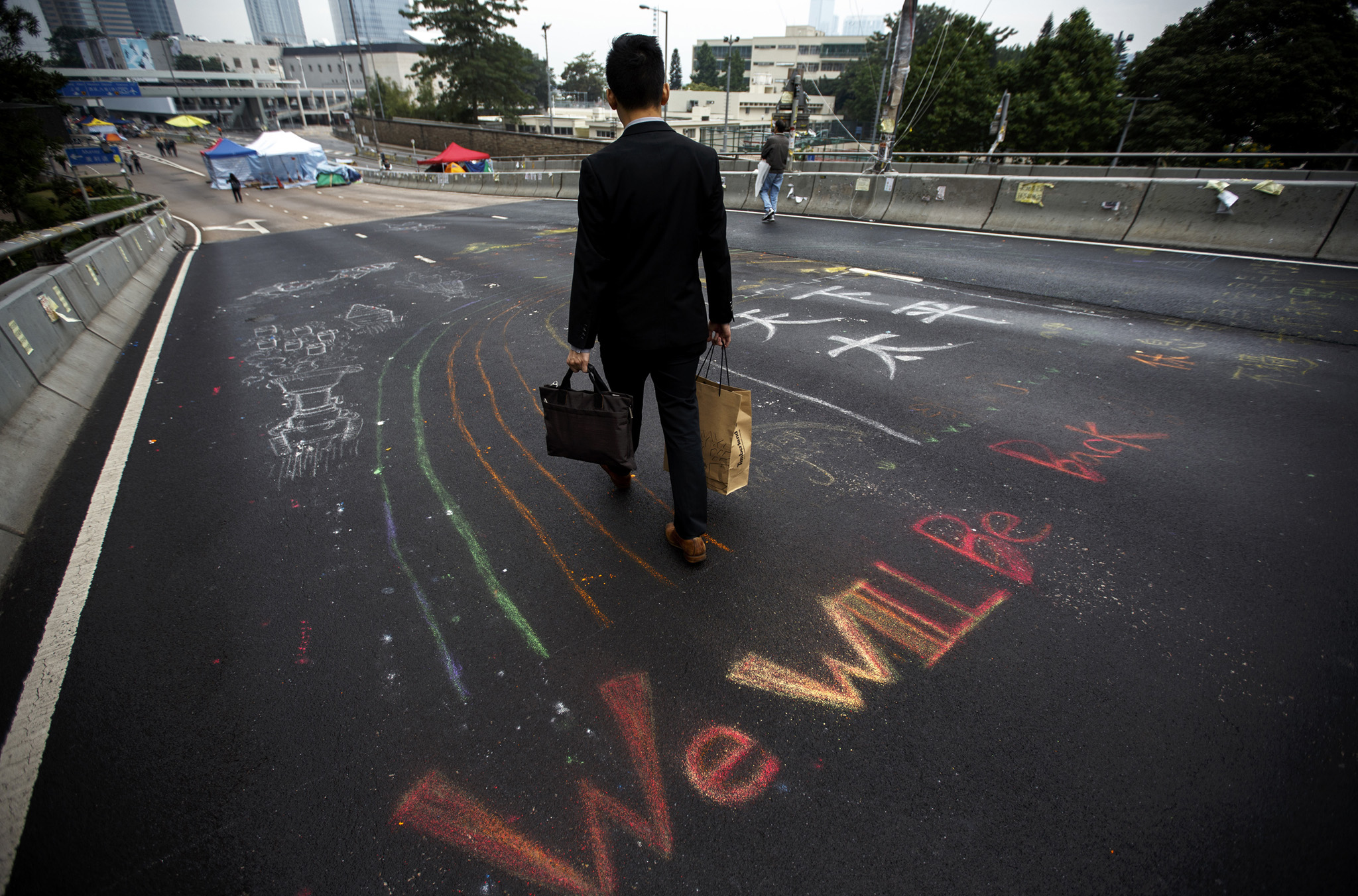 A man walks past a message written on an overpass by pro-democracy protesters at the financial Central district in Hong Kong