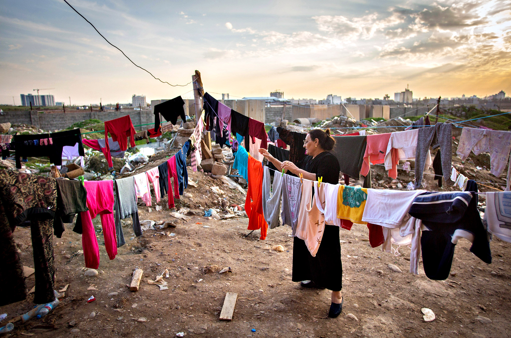 An Iraqi Christian, who fled from her home because of Islamic State's advance earlier this year, hangs up washed clothes to dry besides a displaced persons camp near Umm al-Nour Church, which is now home to hundreds of displaced Iraqi Christians in Erbil, Iraq.  Although the autonomous Kurdistan region in northern Iraq was already a refuge for an estimated 250,000 Syrian refugees, since the Islamic State began its onslaught on Iraq in June, Kurdistan has also taken in a more than one and a half million displaced people. Many have been placed in purpose-built refugee camps but the huge numbers mean thousands of others are forced to live in un-finished buildings or inadequate, makeshift shelters and as winter in the region closes in, there are growing concerns for the welfare of the refugees who, while their homes are still in ISIL controlled territory, have no realistic prospect of returning to them.