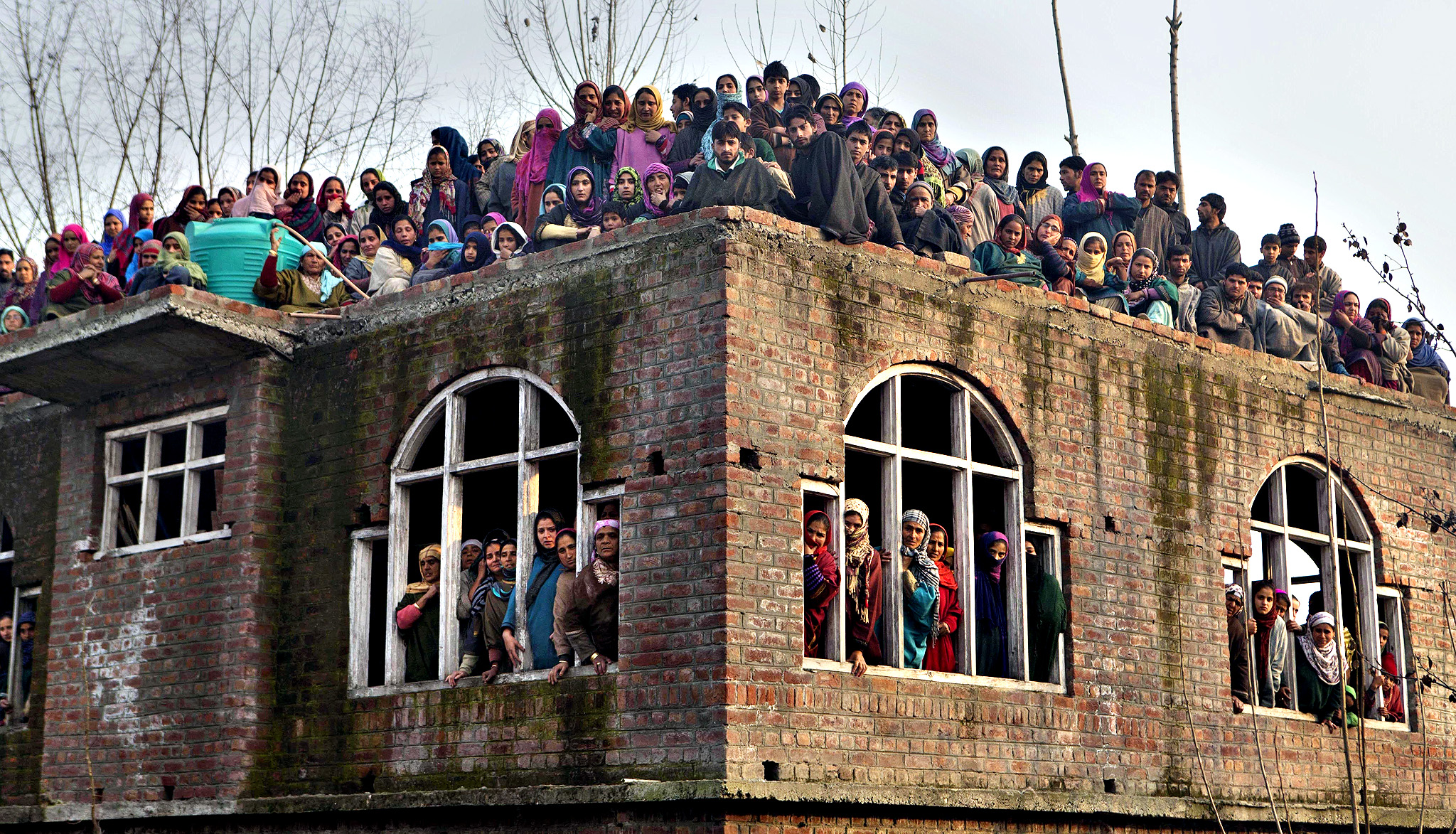 Kashmiri Muslims watch the funeral procession of Indian paramilitary soldier Muhammad Shafi Bhat in Buran, some 35 kilometers (22 miles) north of Srinagar, India, Wednesday, Dec. 3, 2014. Thousands took part in the funeral procession of Shafi who was killed in an attack by Maoist rebels in central India on Monday