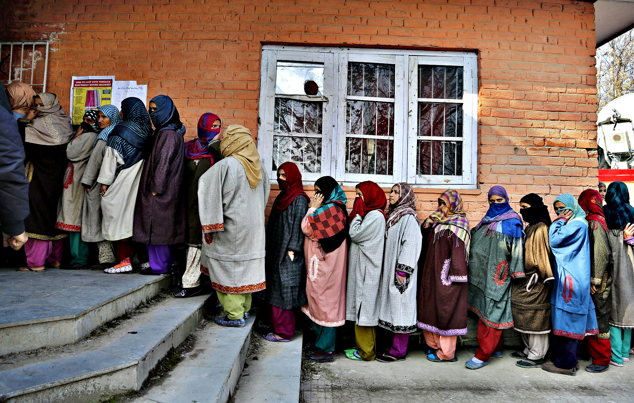 Kashmiri women stand in a queue to cast their votes during the third phase polling of the Jammu and Kashmir state elections in Budgham, about 28 kilometers (17 miles) south west of Srinagar, Indian controlled Kashmir, Tuesday, Dec. 9, 2014. The elections are being held in five stages to allow government forces to better guard against any violence or anti-India protests. Results are due Dec. 23.