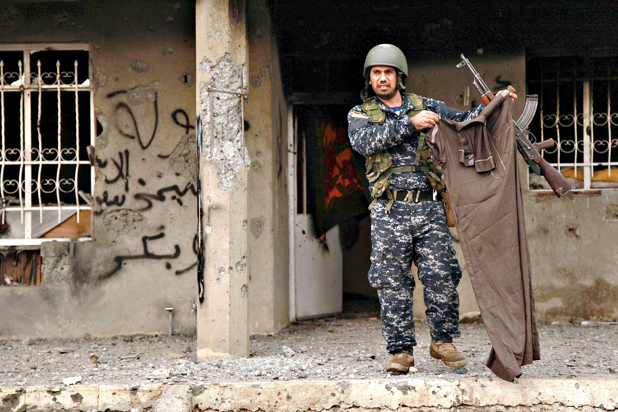 A Kurdish Peshmerga fighter holds up a piece of clothing worn by an Islamic State fighter in Kesarej village, south of Zumar, Nineveh province. Kurdish peshmerga fighters have fought their way to Iraq's Sinjar mountain and freed hundreds of people trapped there by Islamic State fighter. The assault, backed by U.S. air strikes, ended the months-long ordeal of hundreds of people from Iraq's Yazidi religious minority, who had been besieged on the mountain since Islamic State stormed Sinjar and other Kurdish-controlled parts of northern Iraq in August.