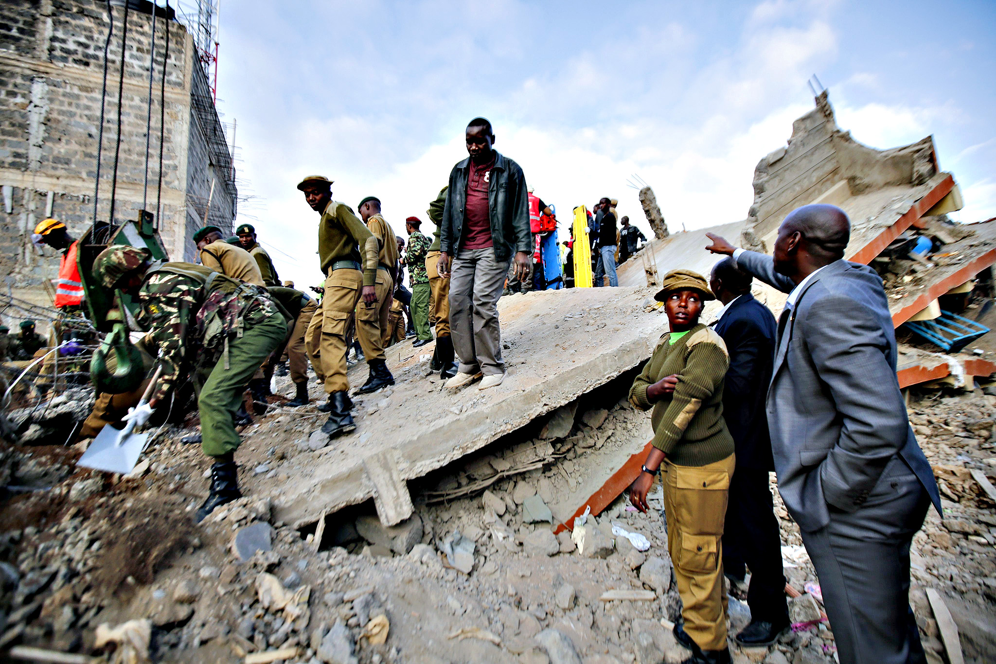 Rescue workers gather around a collapsed building in Makongeni area of Nairobi, Kenya. Several people are feared trapped or dead after a five-storey residential building collapsed in the early hours of Wednesday. The cause of the collapse in unknown