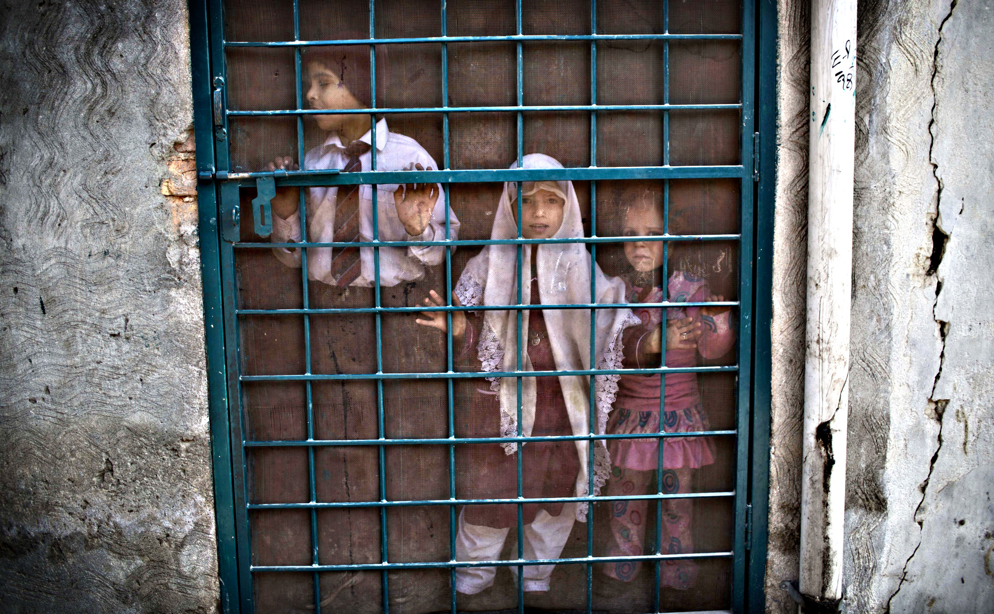 Pakistani schoolchildren look out the doorway of their school, before a special class about the victims killed in Tuesday's Taliban attack on a military-run school in Peshawar, at Ranrra school in Rawalpindi, Pakistan, Friday, Dec. 19, 2014. Pakistani jets and ground forces killed 67 militants in a northwestern tribal region near the Afghan border, officials said Friday, days after Taliban fighters killed 148 people   most of them children   in a school massacre.