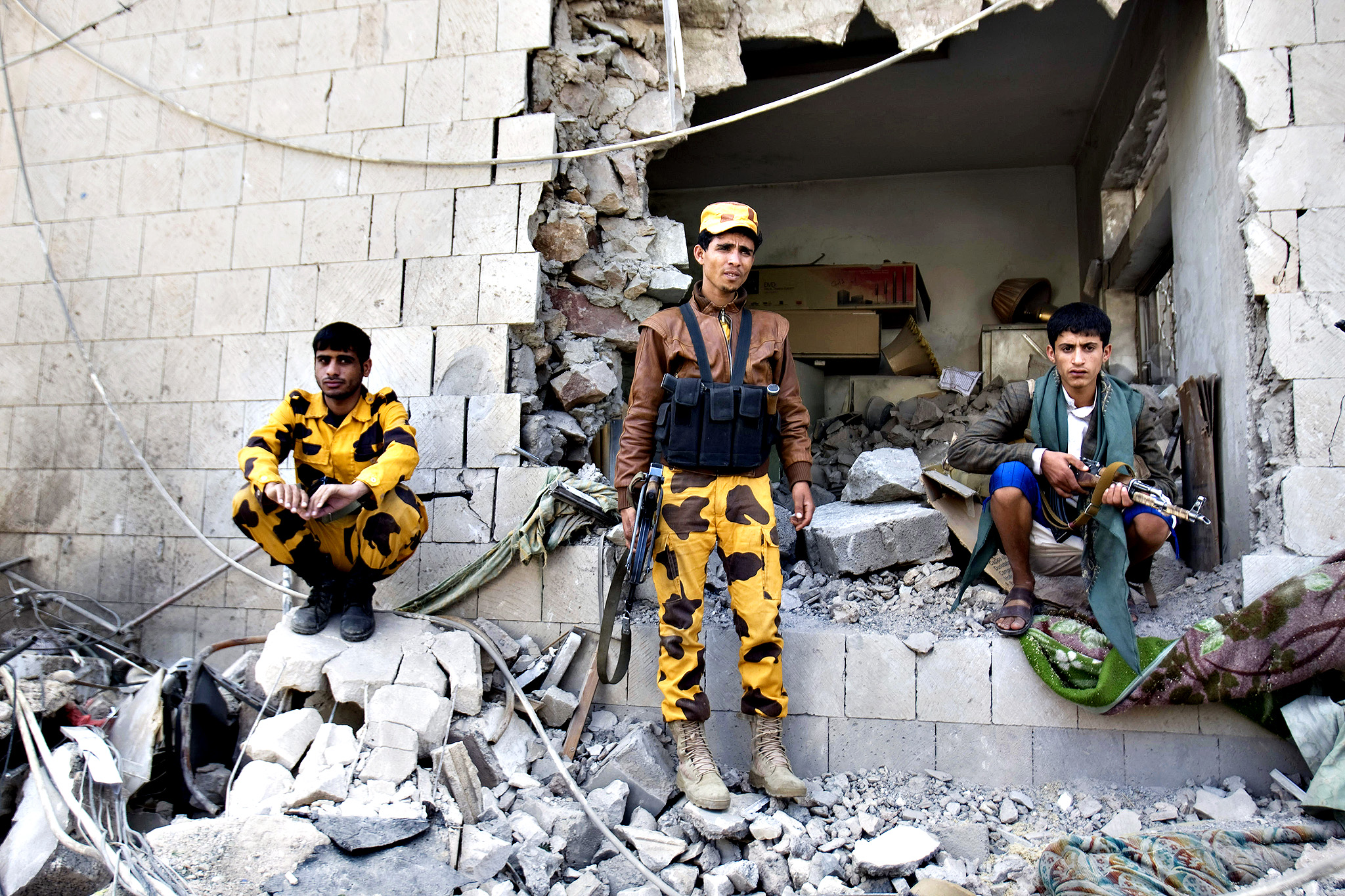 Yemeni police gather at the damaged residence of the Iranian ambassador after a car bomb attack in Sanaa, Yemen, Wednesday, Dec. 3, 2014. A massive car bomb exploded Wednesday morning in the Yemeni capital, Sanaa, apparently targeting the home of the Iranian ambassador, Yemeni security officials said.