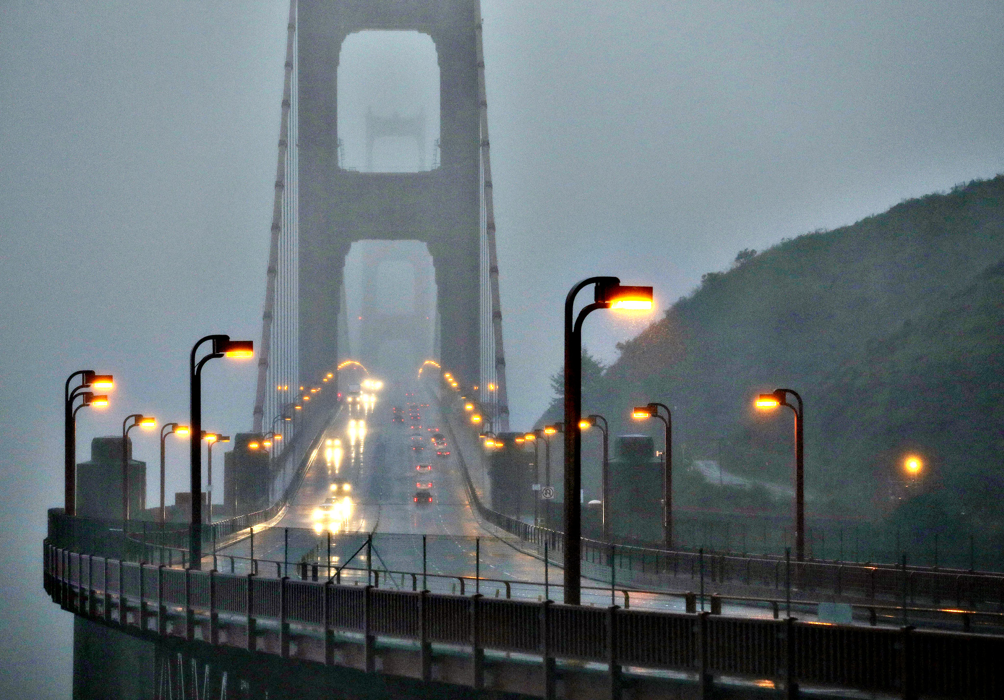 Traffic moves slowly across the Golden Gate Bridge in the high winds and rain Thursday, Dec. 11, 2014, in this view from Sausalito, Calif.  A storm expected to be one of the windiest and rainiest in five years swept across the San Francisco Bay Area on Thursday, knocking out power to tens to thousands and delaying travel by air, train and ferry. Pacific Gas & Electric is reporting outages are widespread across the Bay Area due to weather, but officials weren't immediately available to give a specific number of outages.