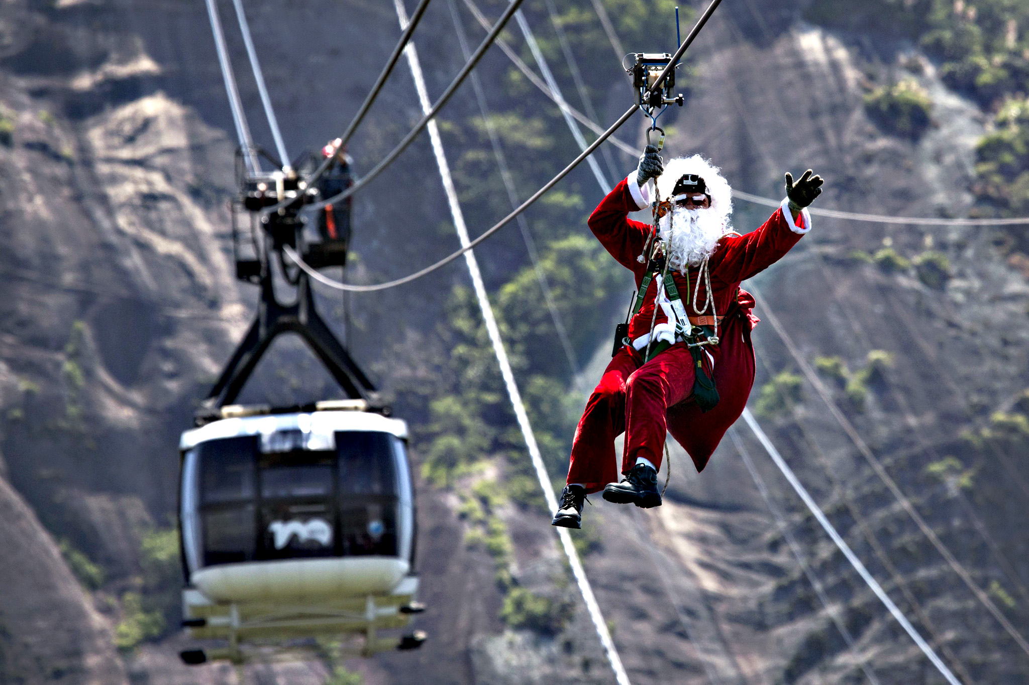 A man dressed as Santa Claus zip lines away from Sugar Loaf mountain after riding on top of a cable car in Rio de Janeiro, Brazil, Thursday, Dec. 18, 2014. The cable car company surprised tourists with a visit from Santa to celebrate Christmas.