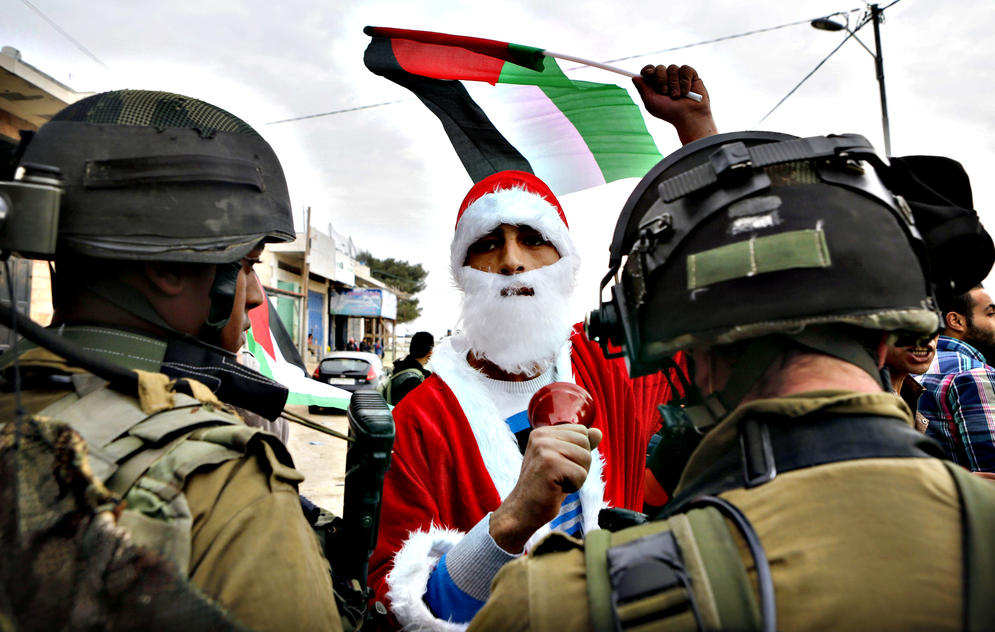 Palestinian protester dressed as Santa Claus holds a Palestinian flag as he argues with Israeli soldiers during a demonstration against Israeli settlements in the village of Maasara near the West Bank city of Bethlehem...A Palestinian protester dressed as Santa Claus holds a Palestinian flag as he argues with Israeli soldiers during a demonstration against Israeli settlements in the village of Maasara near the West Bank city of Bethlehem December 19, 2014.