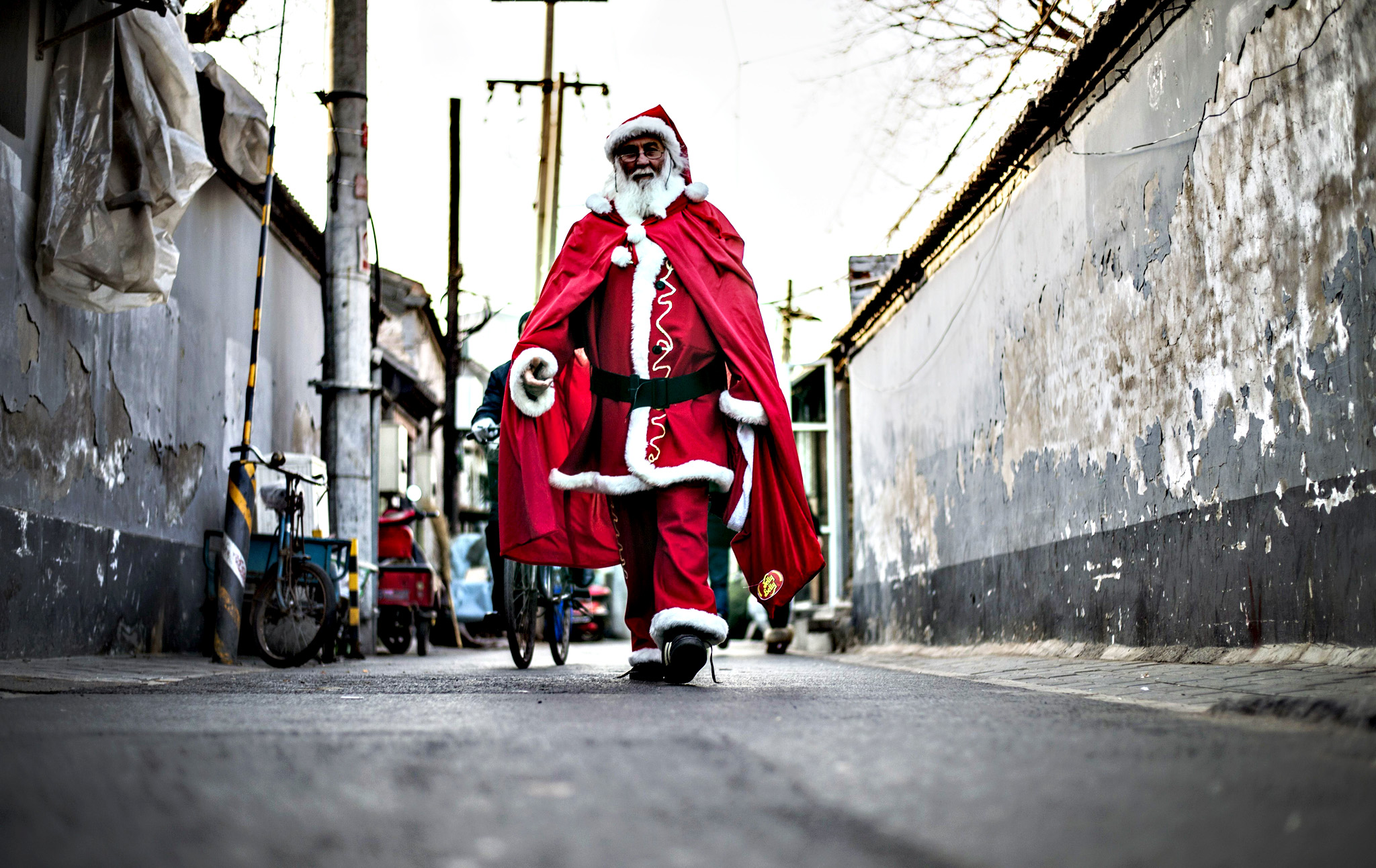 A Santa Claus walks in a hutong, in Beijing on December,23, 2014 as Christians around the world prepare to celebrate the holy day
