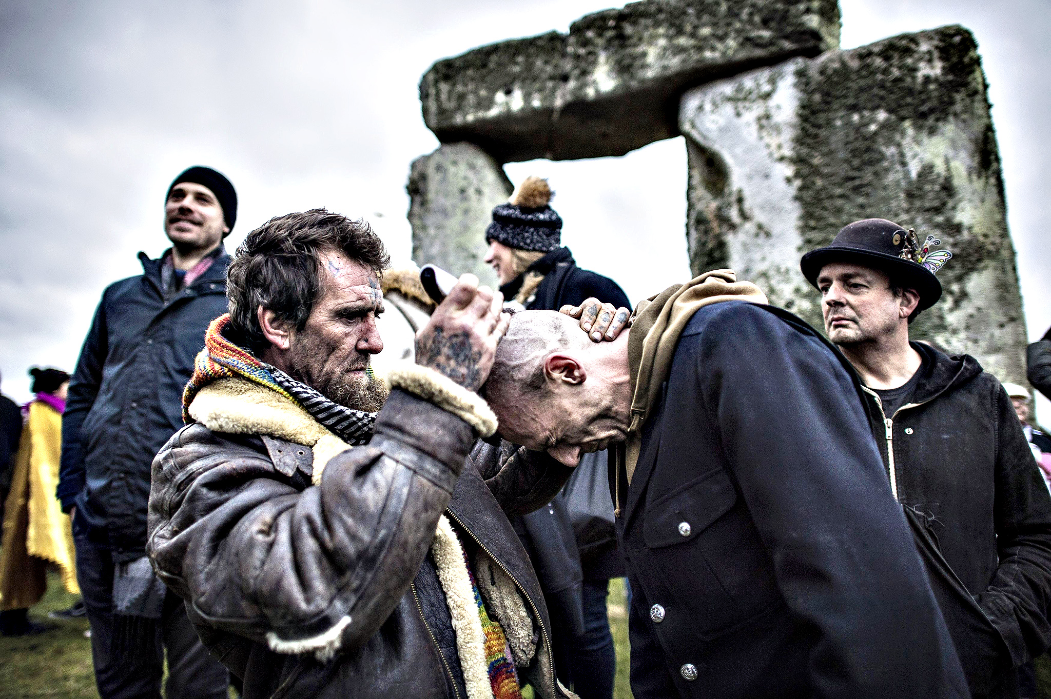 A man has his head shaved inside the stone circle at Stonehenge, Witshire, where people are gathering to celebrate the Winter solstice.