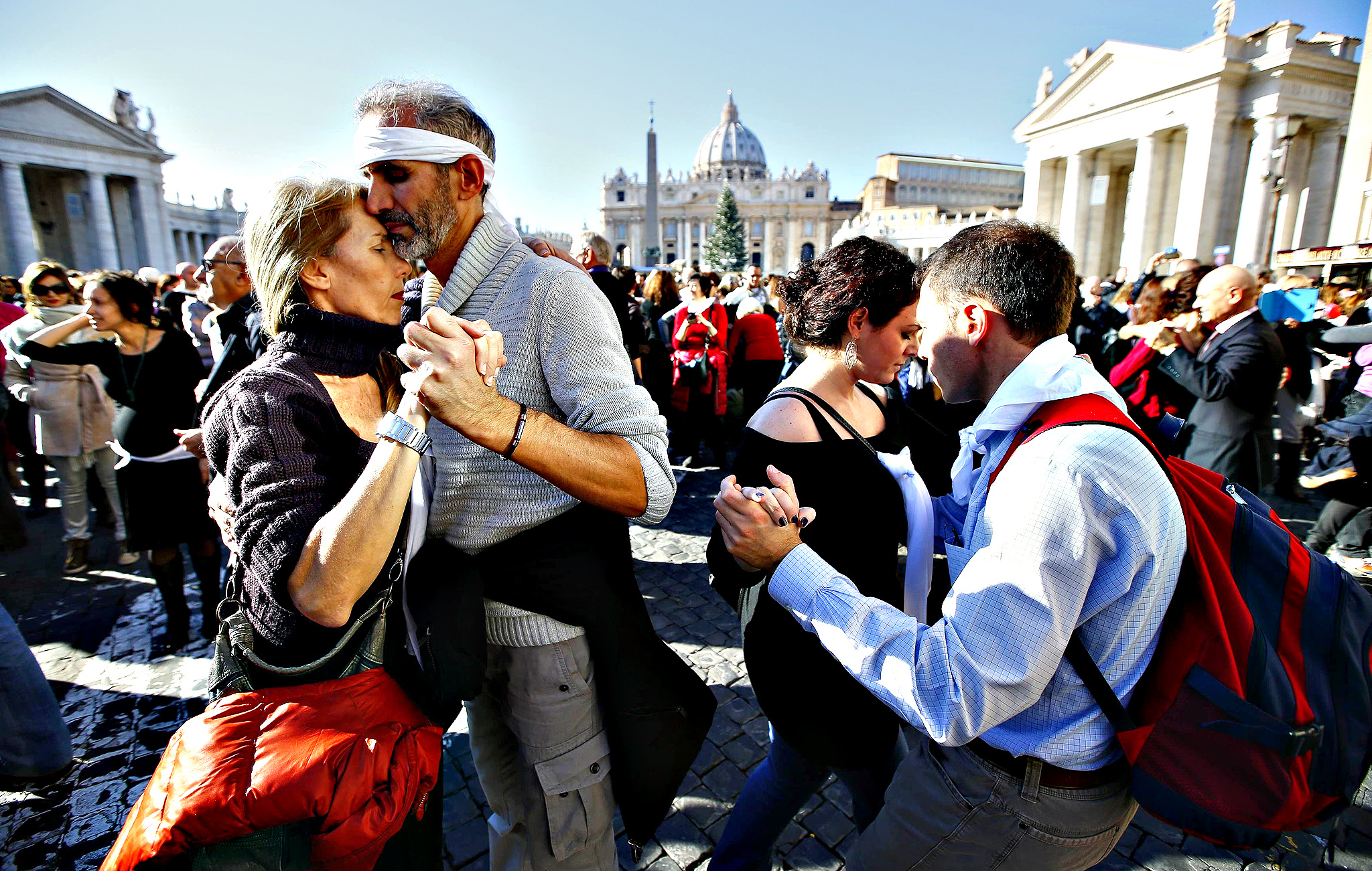 "Couples dance a tango in front of Saint Peter's basilica at the Vatican, December 17, 2014. At the rear edge of the square more than 2,000 people, who came to Rome from all over Italy for the 78th birthday of Pope Francis, danced in ""A tango for Pope Francis"" event as music blared."