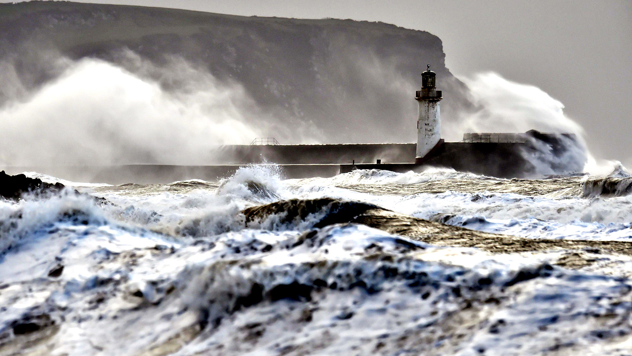 "Giant waves hit the lighthouse wall in Whitehaven, as the stormy weather is causing disruption across parts of the UK with power cuts, ferry and train cancellations and difficult driving conditions. PRESS ASSOCIATION Photo. Picture date: Wednesday December 10, 2014. The Met Office has issued an amber ''be prepared'' warning for the west coast of Scotland, the Highlands and Islands, Orkney, Shetland and Northern Ireland as a so-called ""weather bomb"" batters the country"