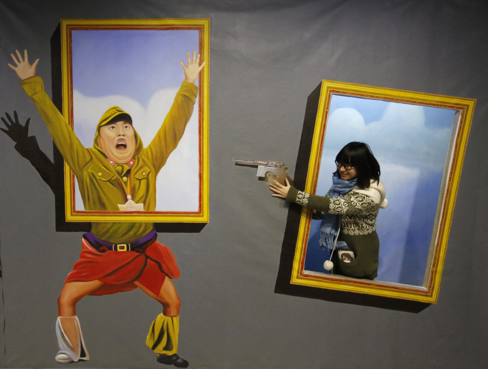 A visitor poses for a photograph in front of a 3D painting depicting a Japanese Imperial army soldier at a 3D art gallery in Beijing...A visitor poses for a photograph in front of a 3D painting depicting a Japanese Imperial army soldier at a 3D art gallery in Beijing January 16, 2015. The gallery attracts visitors with various 3D paintings and installations depicting world famous political