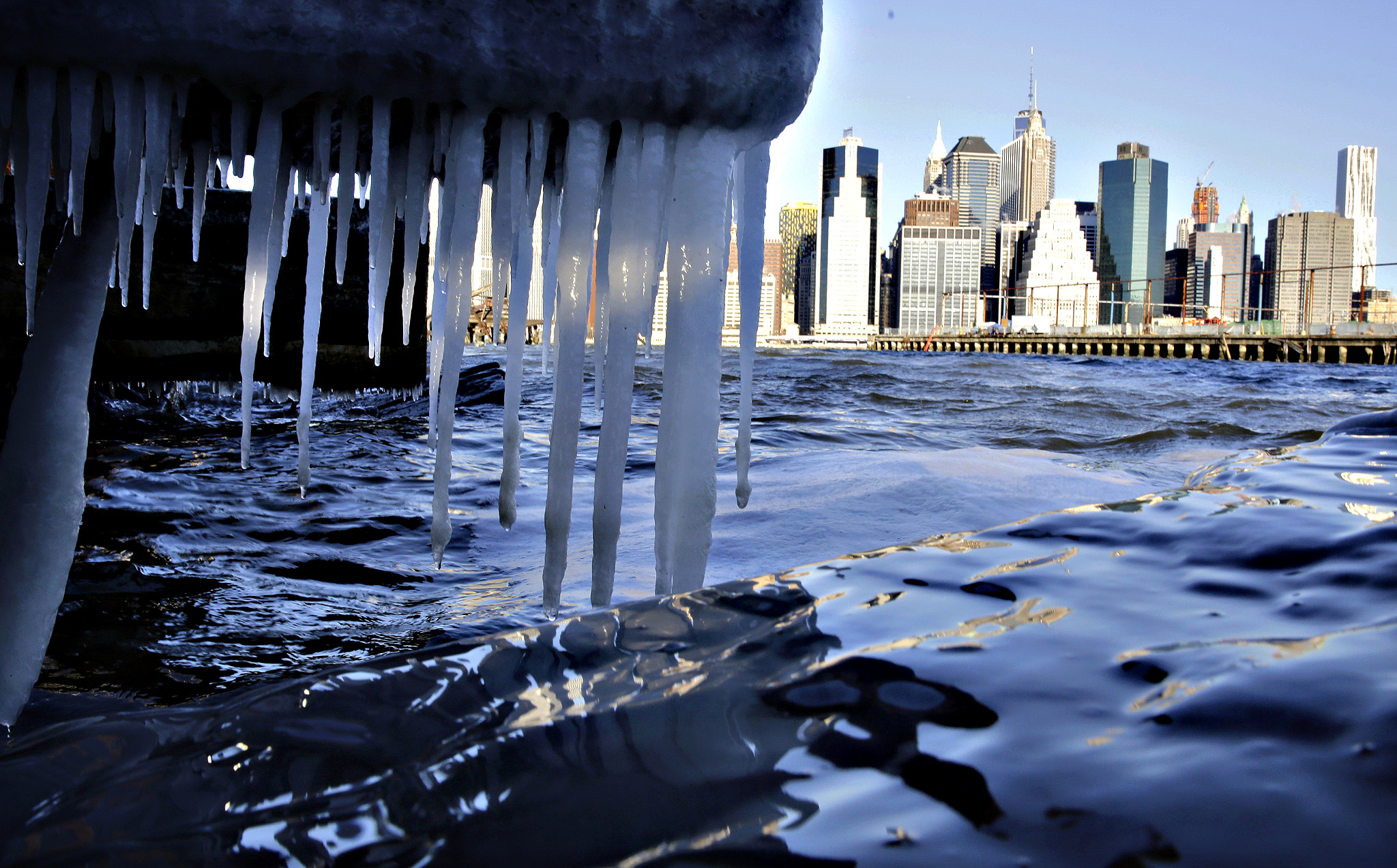Icicles form on the waterfront in the borough of Brooklyn in New York on Thursday, Jan. 8, 2014. Cold air has sent temperatures plummeting into the single digits around the U.S., with wind chills driving them even lower. Lower Manhattan appears in the background.