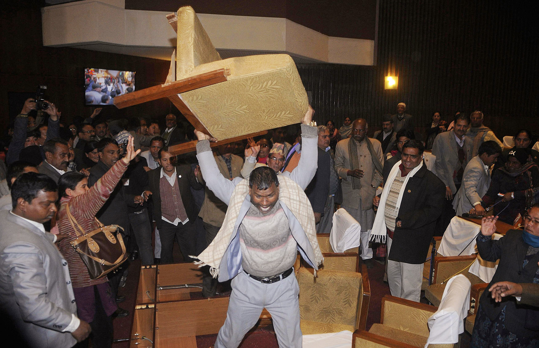 A constitution assembly member of an opposition party throws a chair during a meeting inside the Constitution Assembly building in Kathmandu...A constitution assembly member of an opposition party throws a chair during a meeting inside the Constitution Assembly building in Kathmandu January 20, 2015. The new assembly was elected to write a constitution after the abolition of the 240-year-old feudal monarchy that the Maoists fought against. REUTERS/Bikash Dware (NEPAL - Tags: POLITICS CIVIL UNREST TPX IMAGES OF THE DAY)
